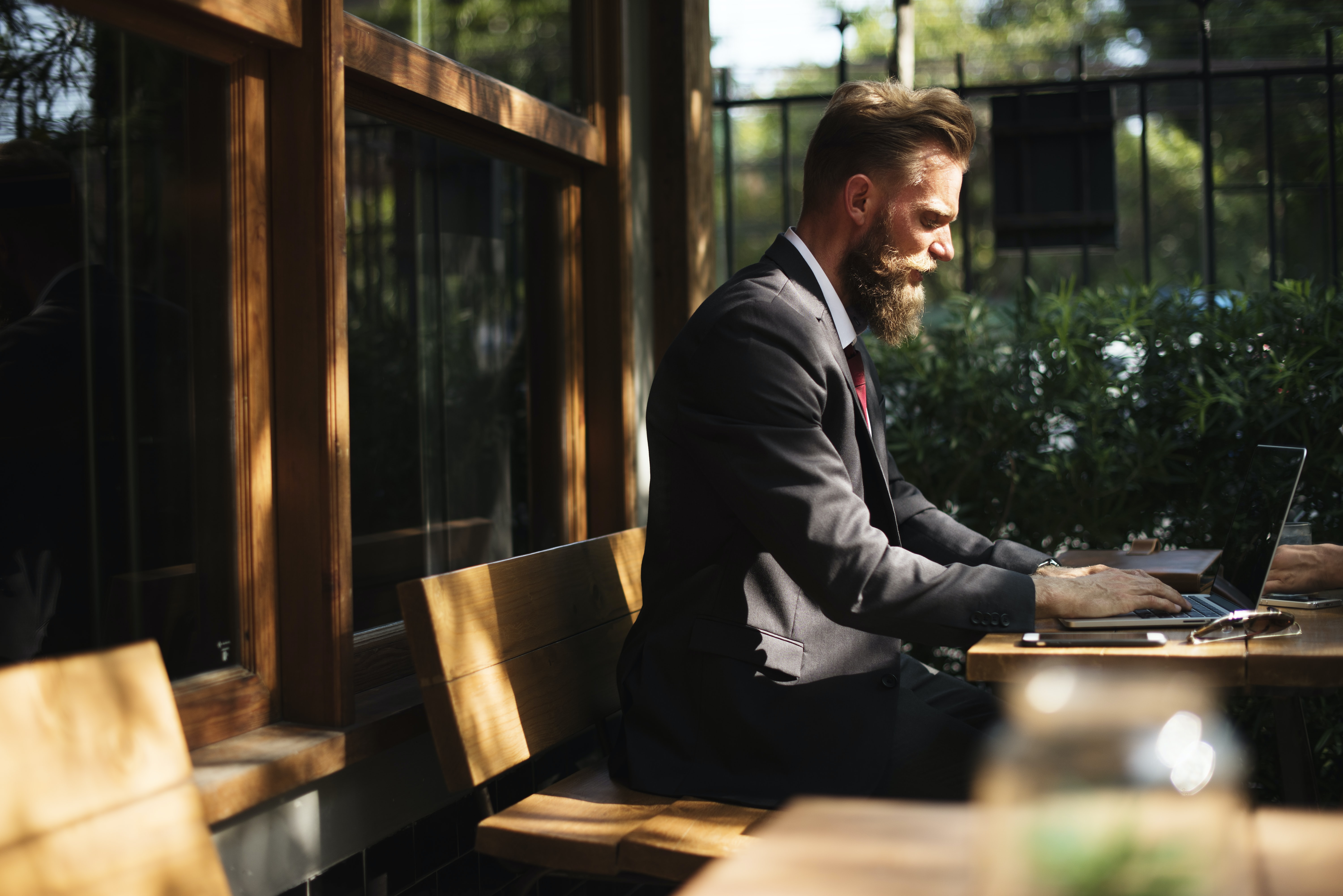 A bearded man wearing a suit sitting outside and working on his laptop at a patio table