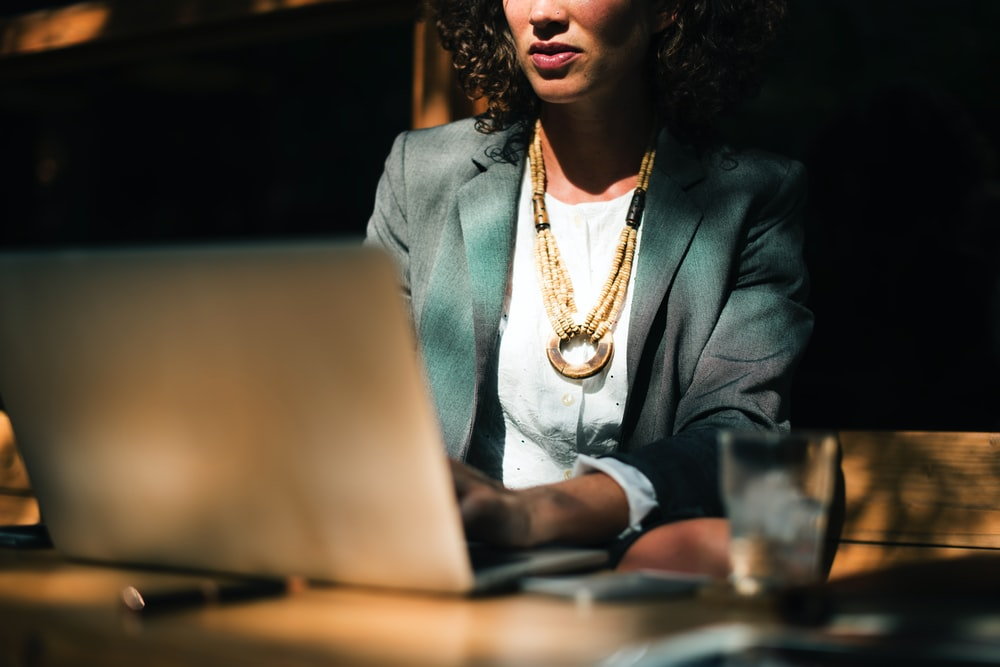 A businesswoman sitting at a table with a laptop and a glass of water