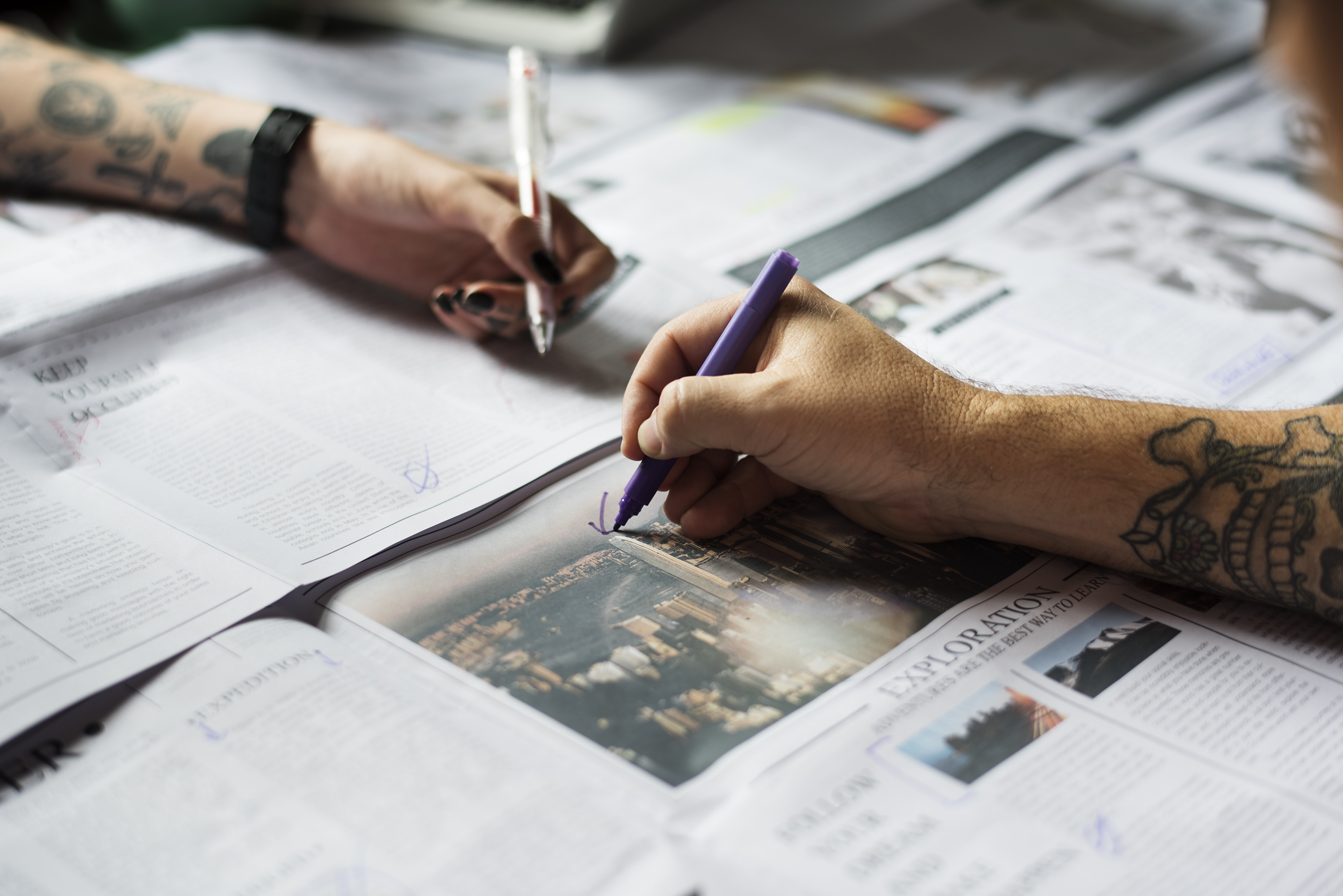 Two people with tattoos on their arms drawing in a newspaper