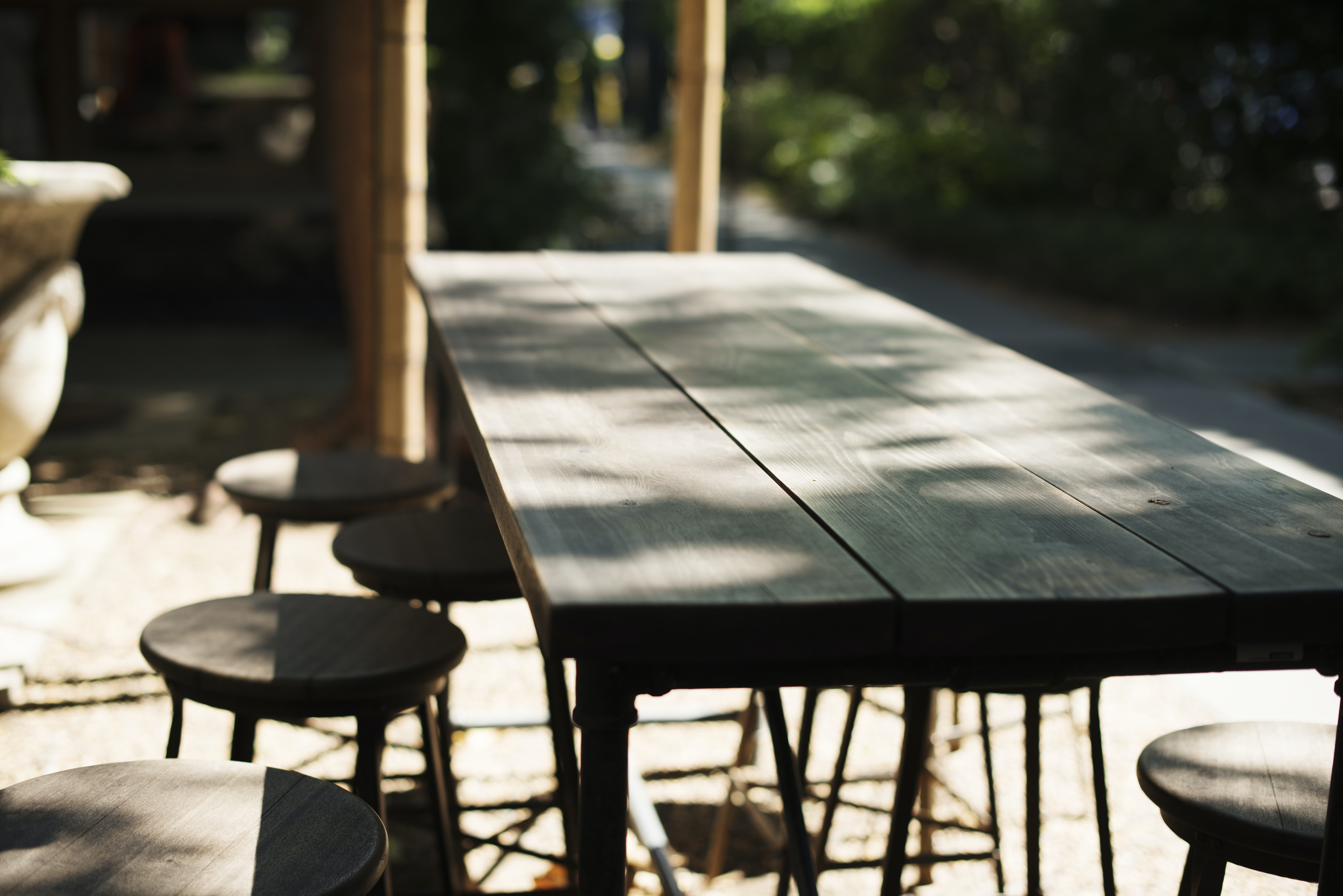 Empty wood table with stools on an outdoor patio