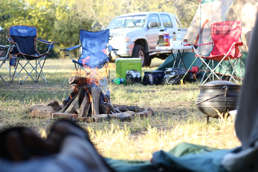 camping chairs in front of bonfire near pickup truck