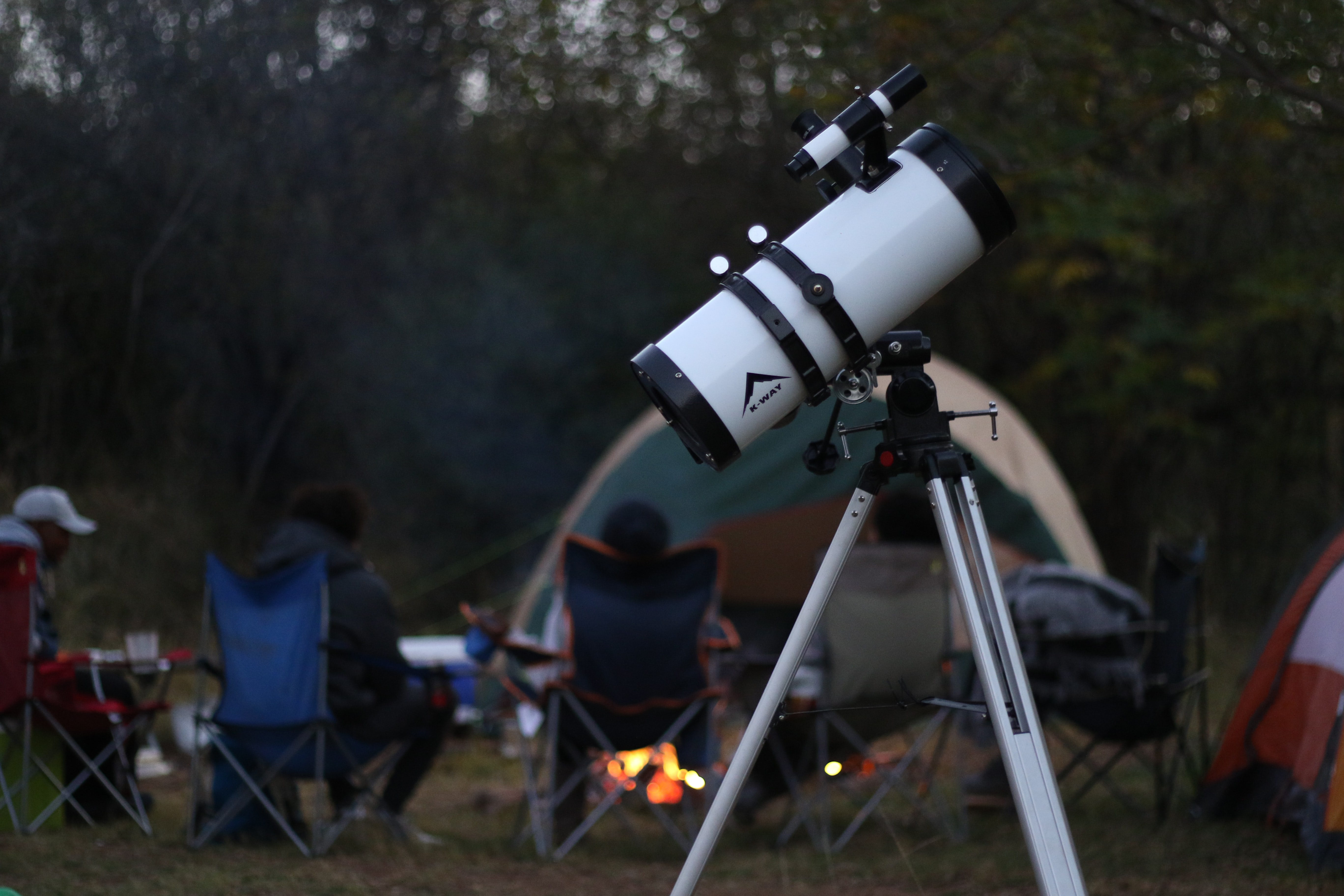 Campers sitting around a campfire with their stargazing telescope set up behind them
