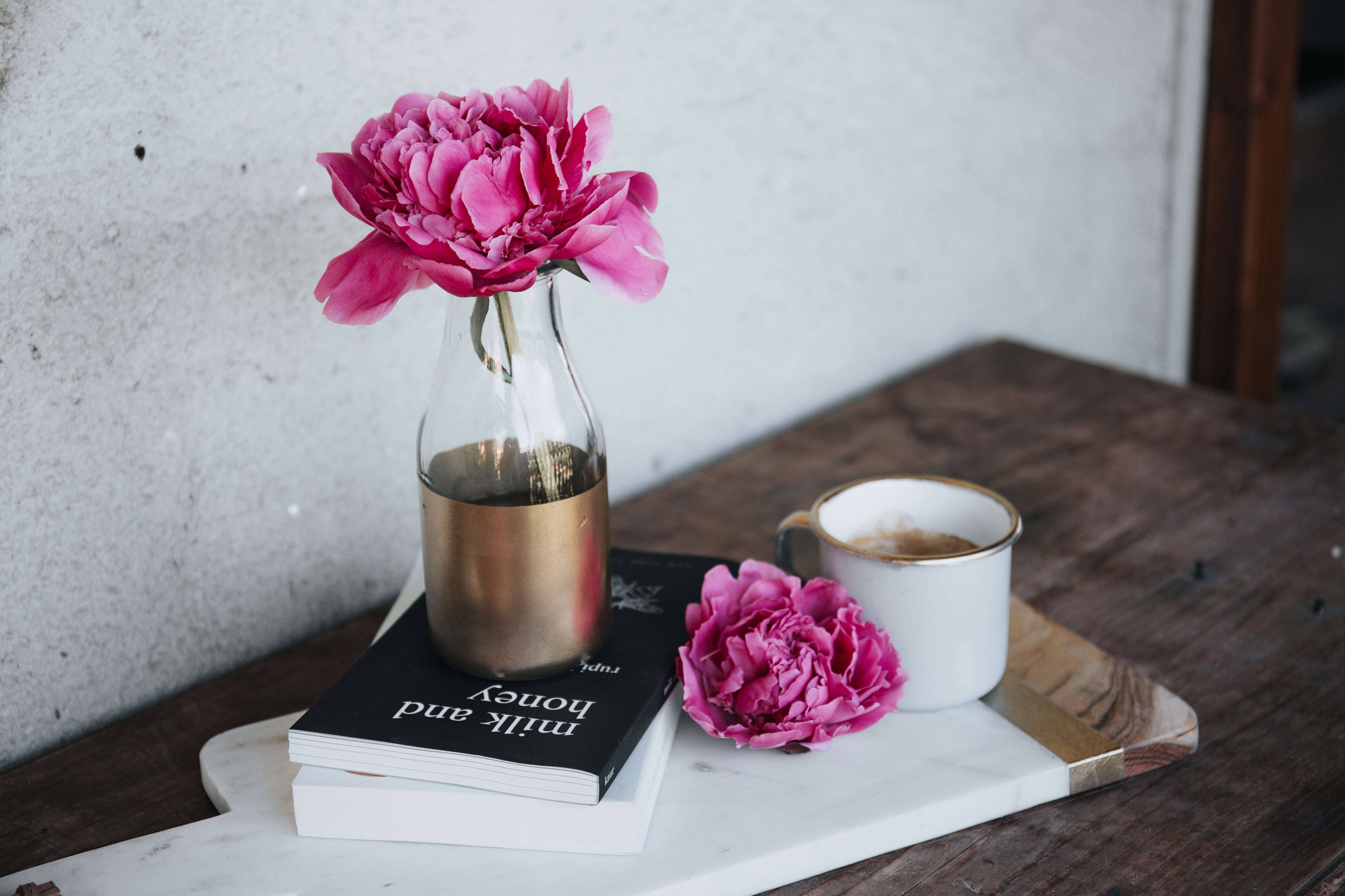Intensely pink flowers in a vase standing on a book on a wooden chopping board