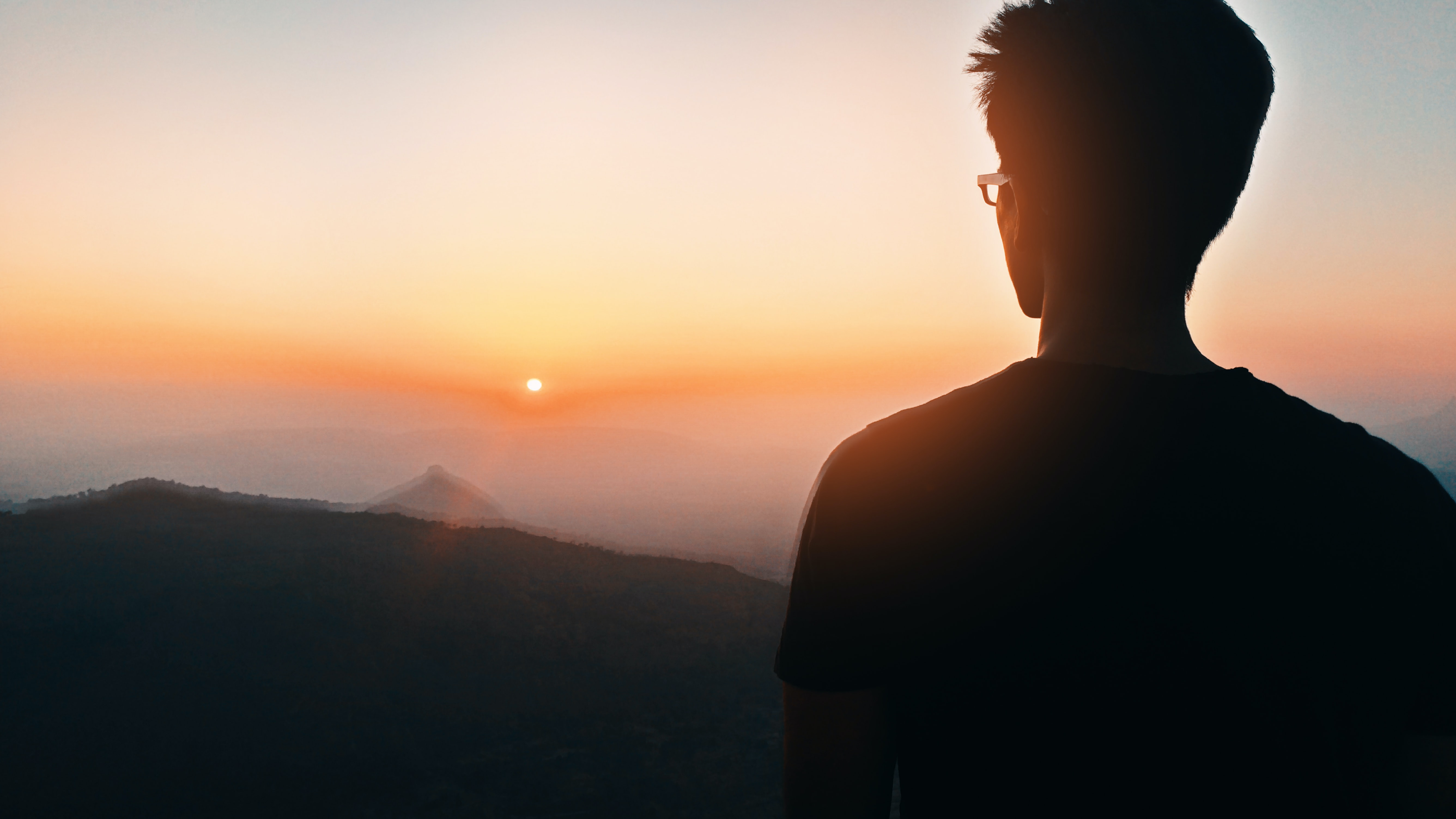man's silhouette facing mountain at golden hour