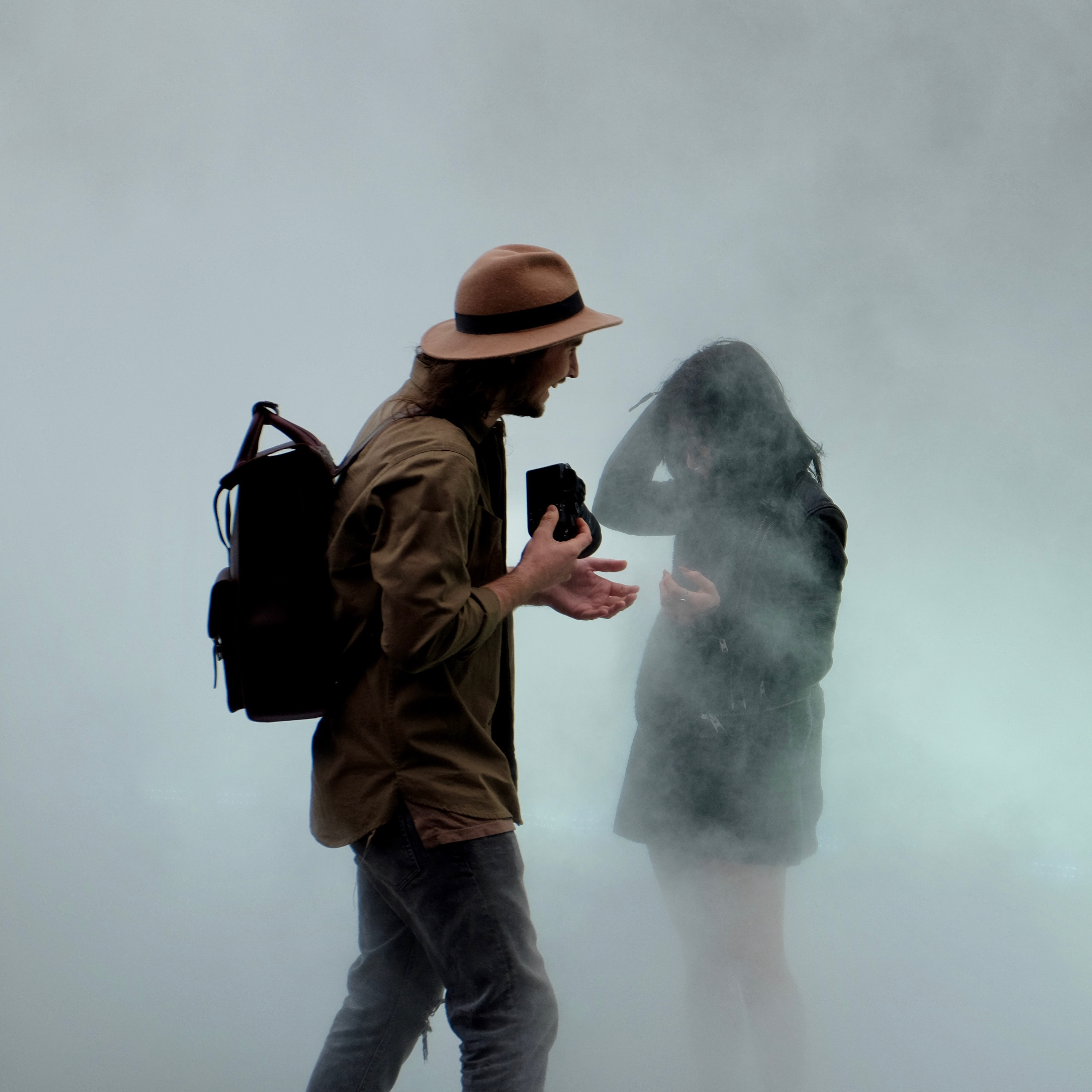 Man and woman in hiking gear laugh in the fog