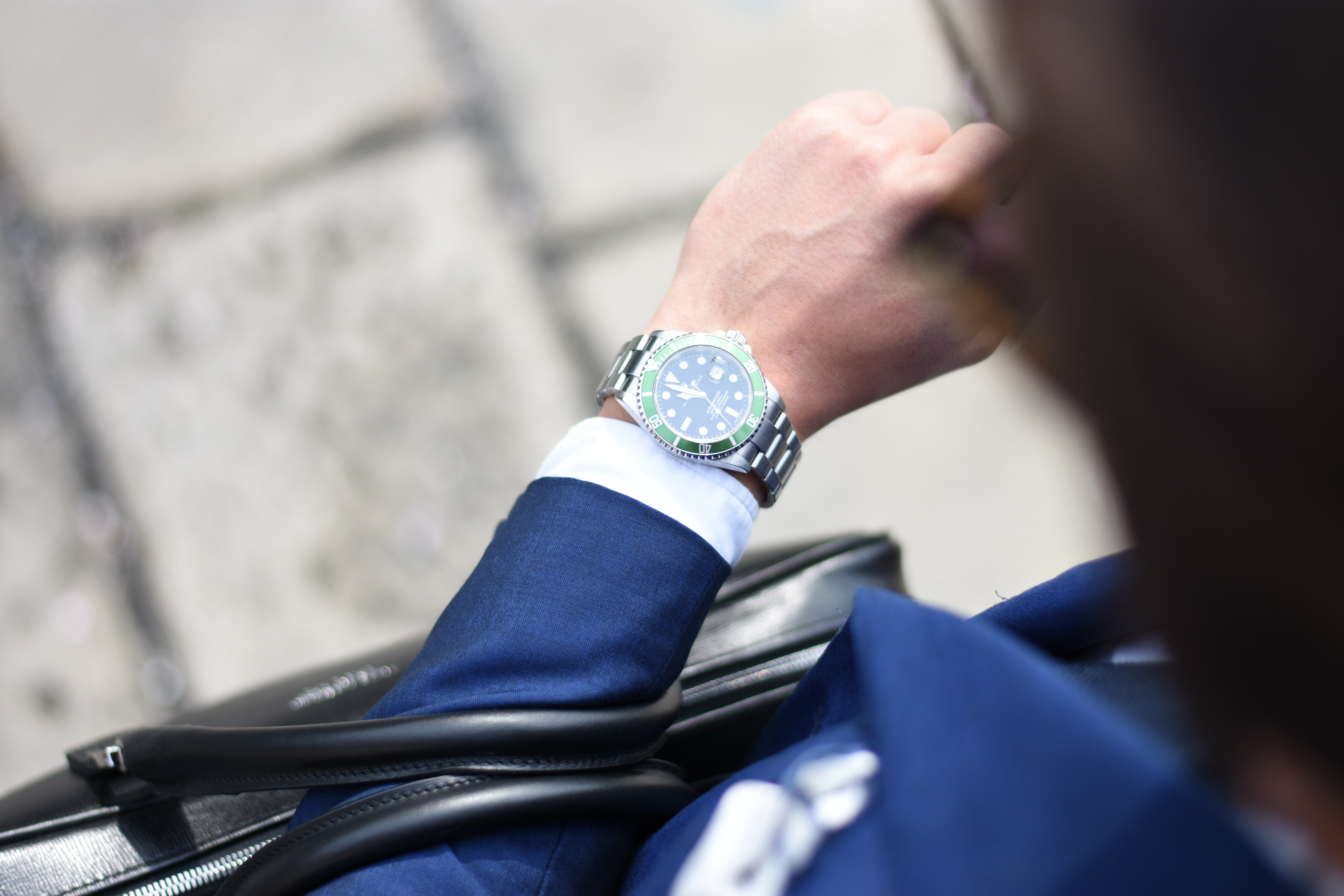 An overhead shot of a man in a navy blue suit looking at his elegant watch