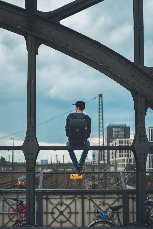man sitting on top of bridge
