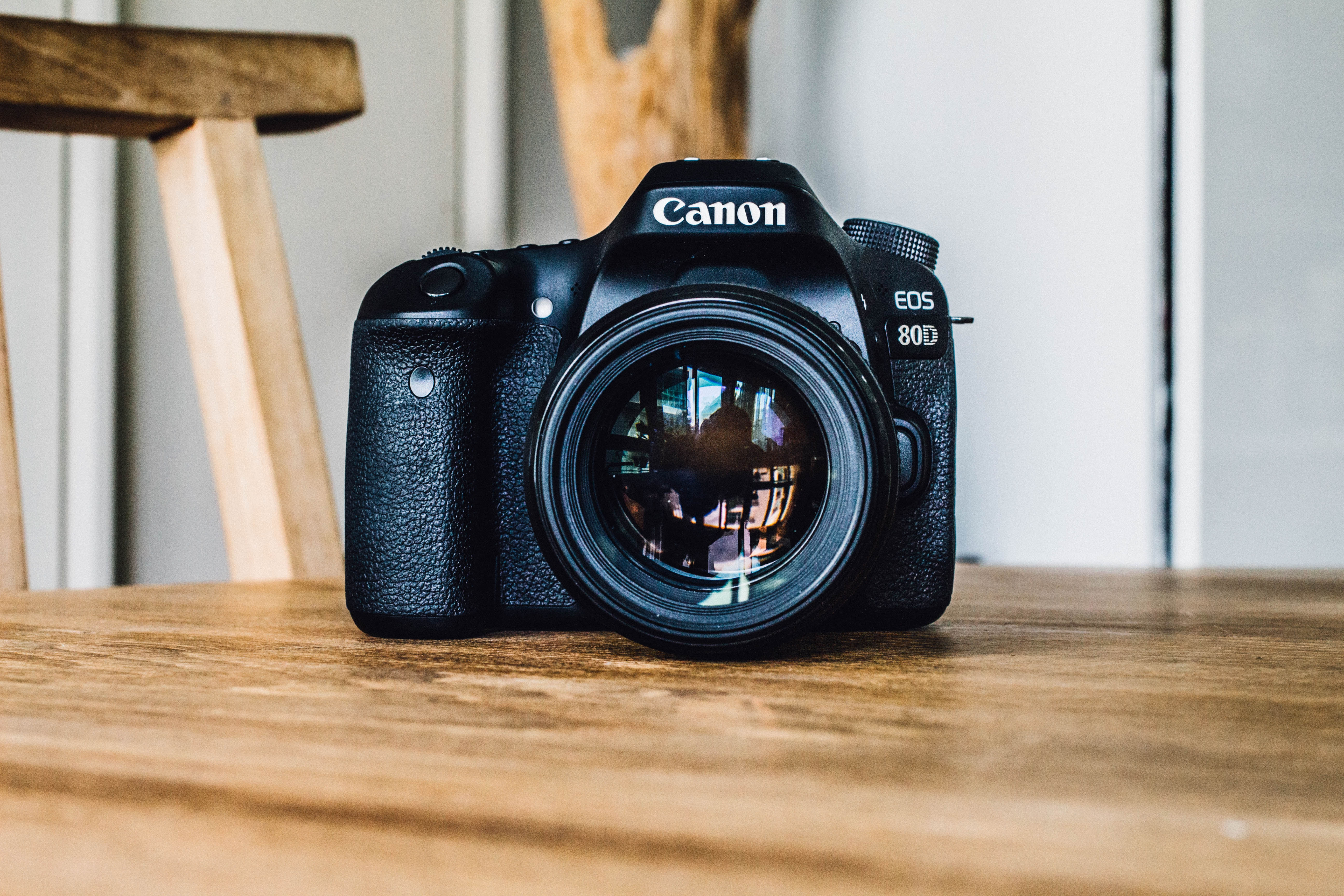 Canon EOS 80D camera on a wooden table by a wooden chair