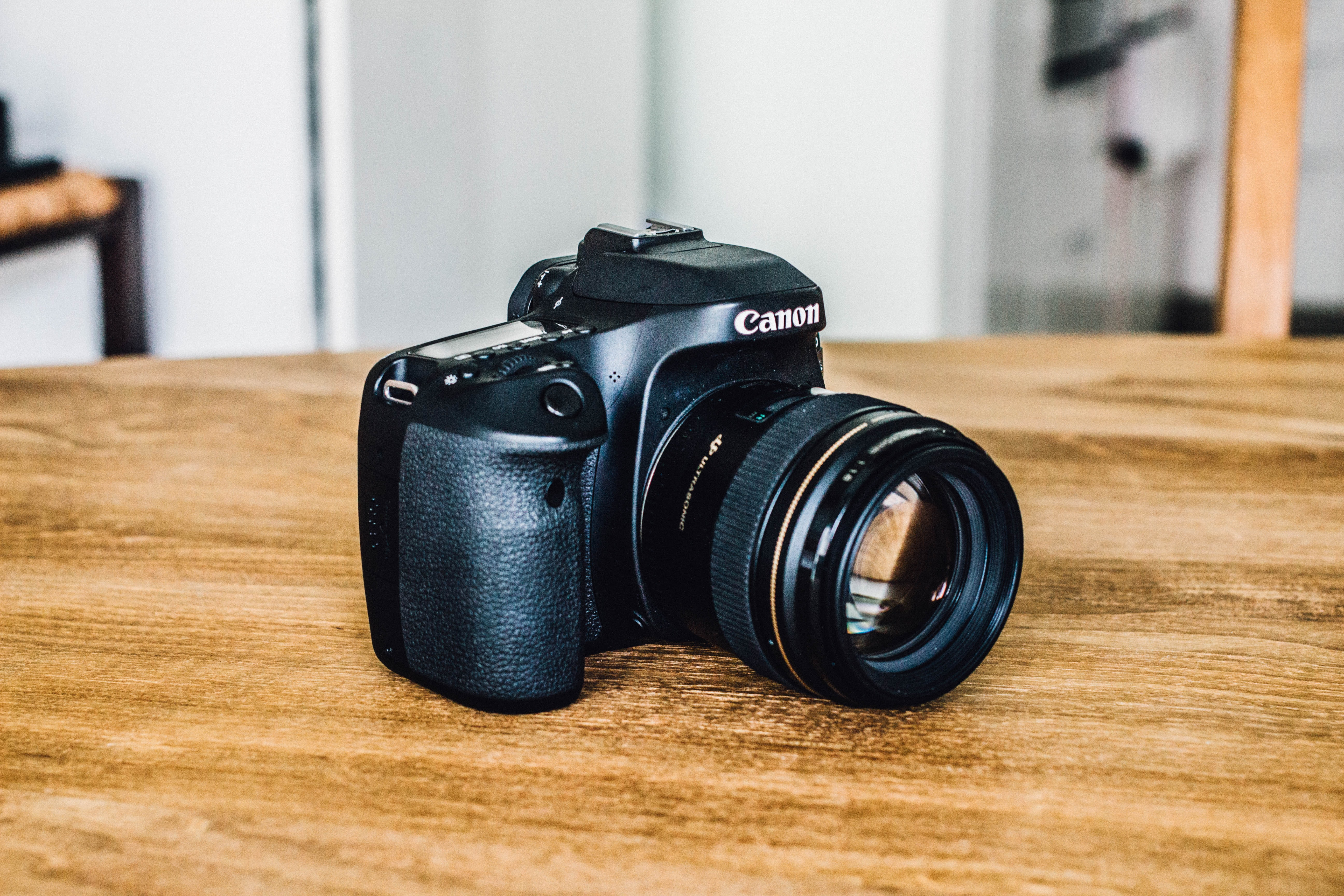 black Canon DSLR camera on wooden surface