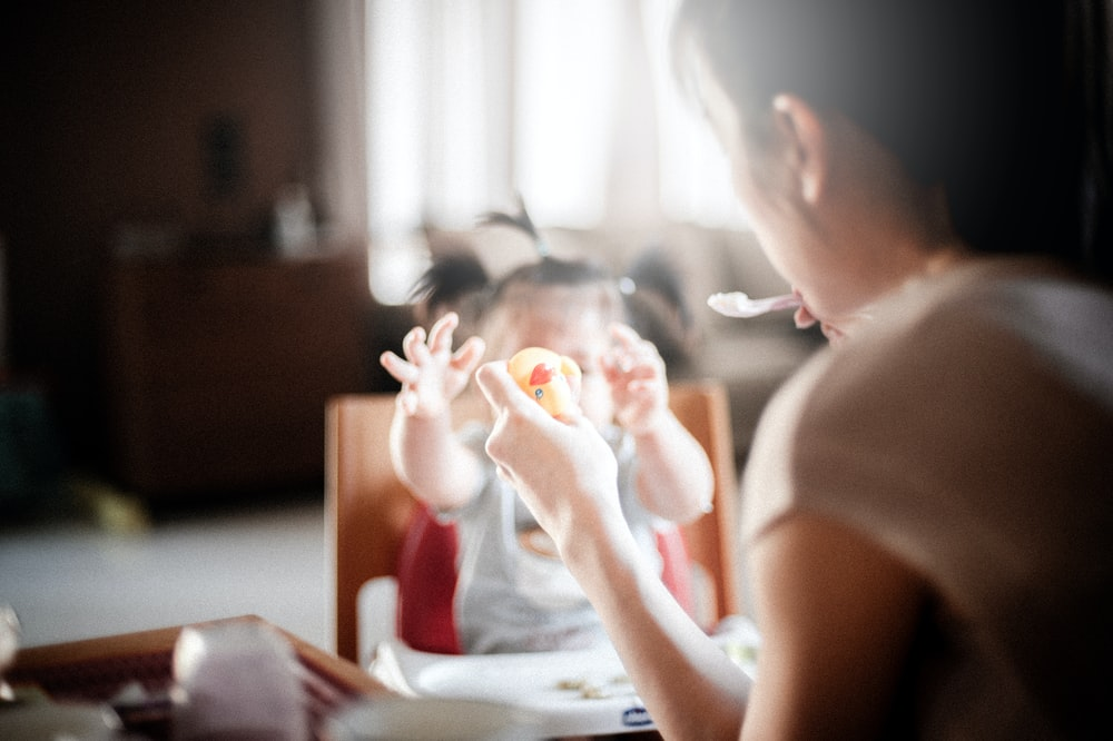 selective focus photography of woman feeding baby