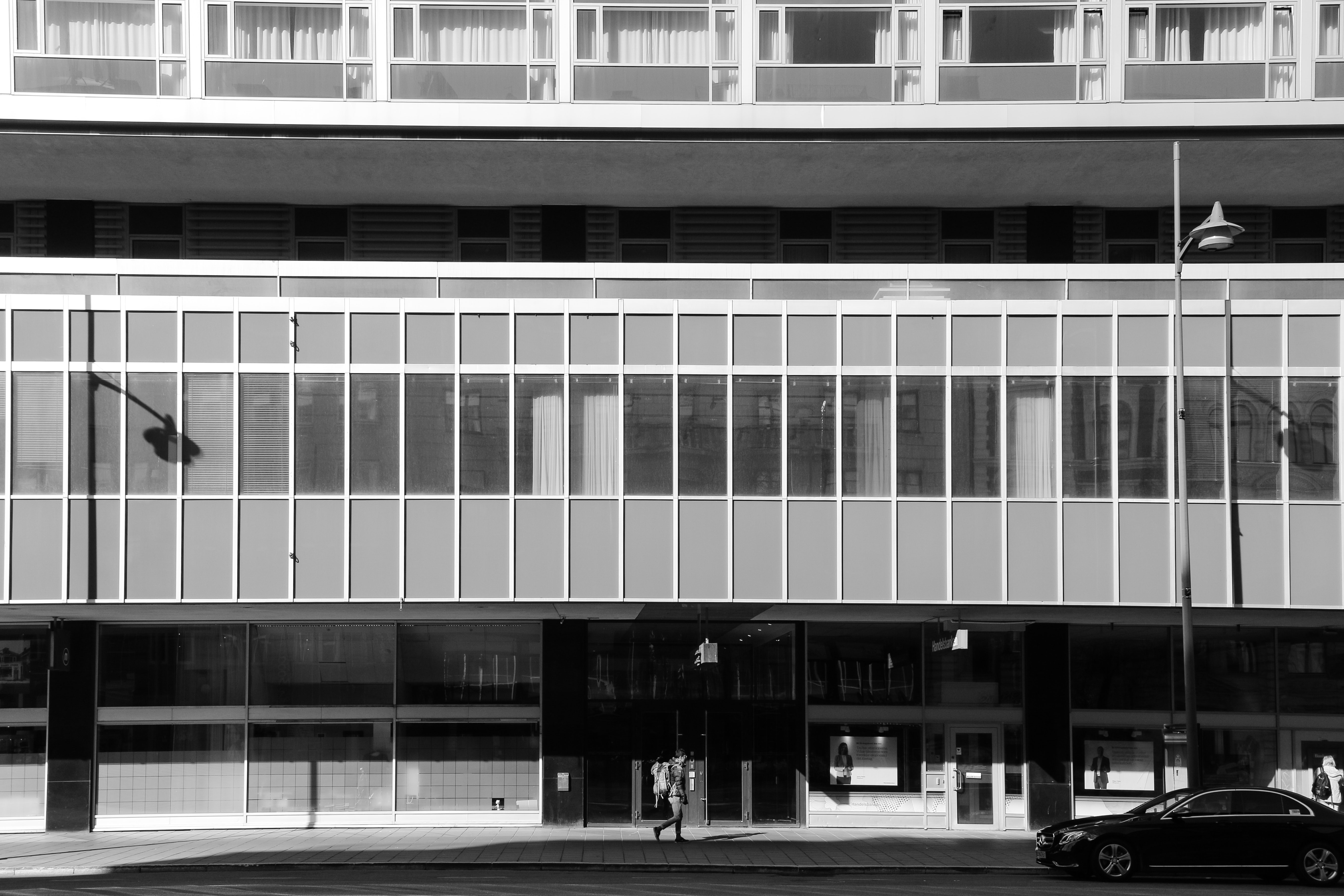 Black and white, modern building with car parked in front
