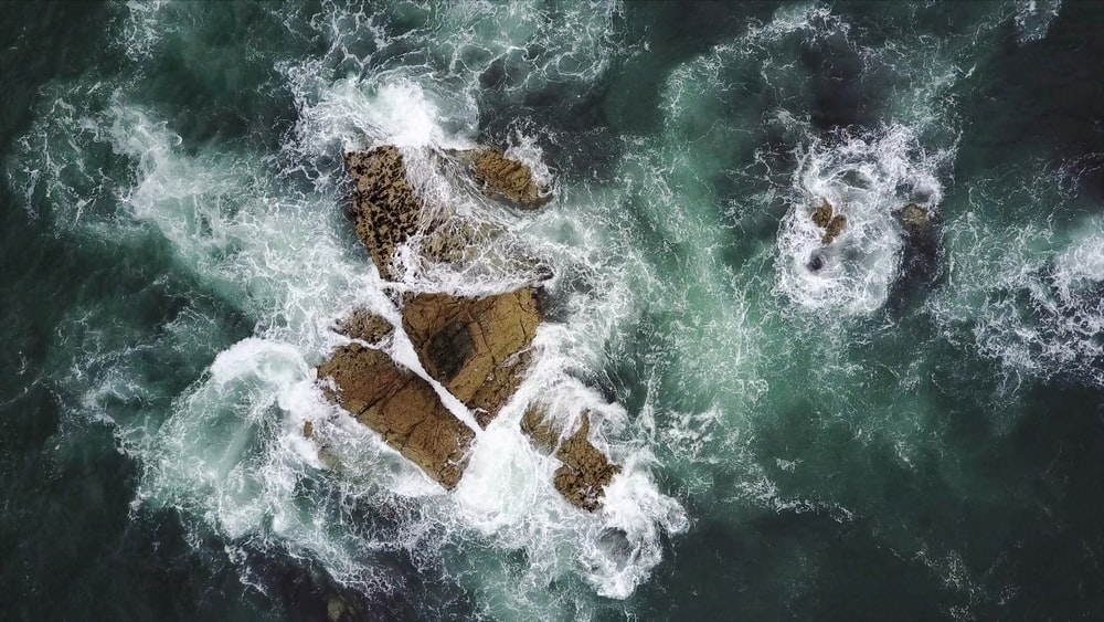 rock formation surrounded by body of water in aerial photography