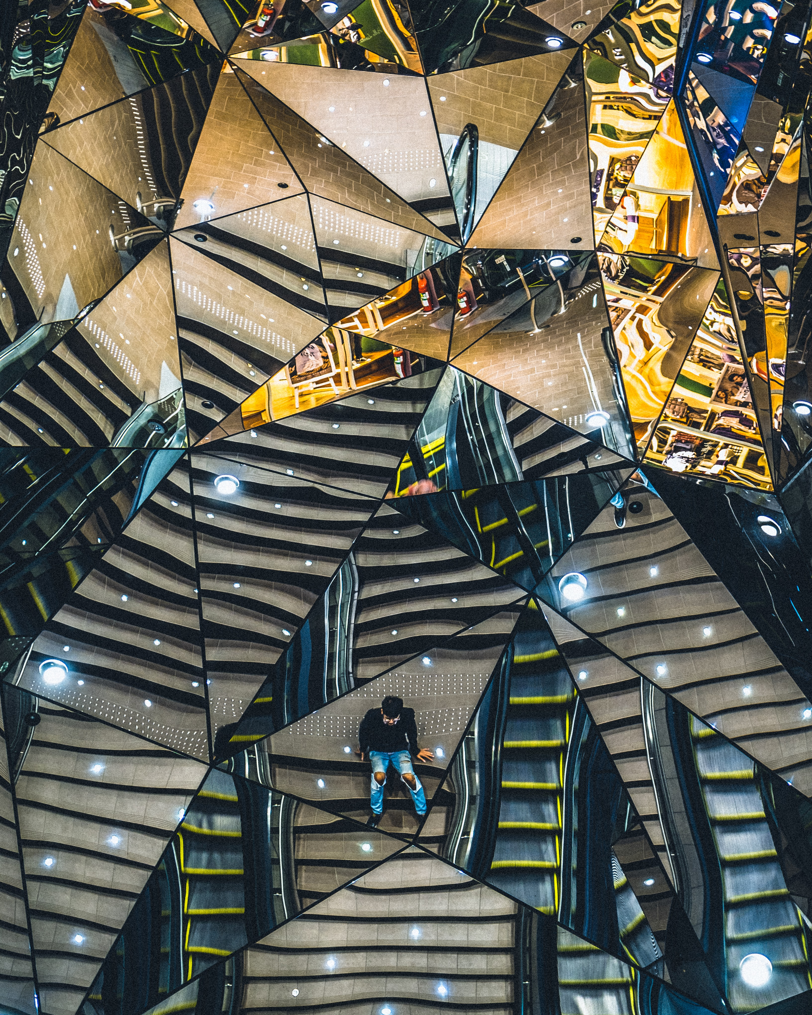 Reflection of a staircase and an elevator in a mirror composed of triangular parts