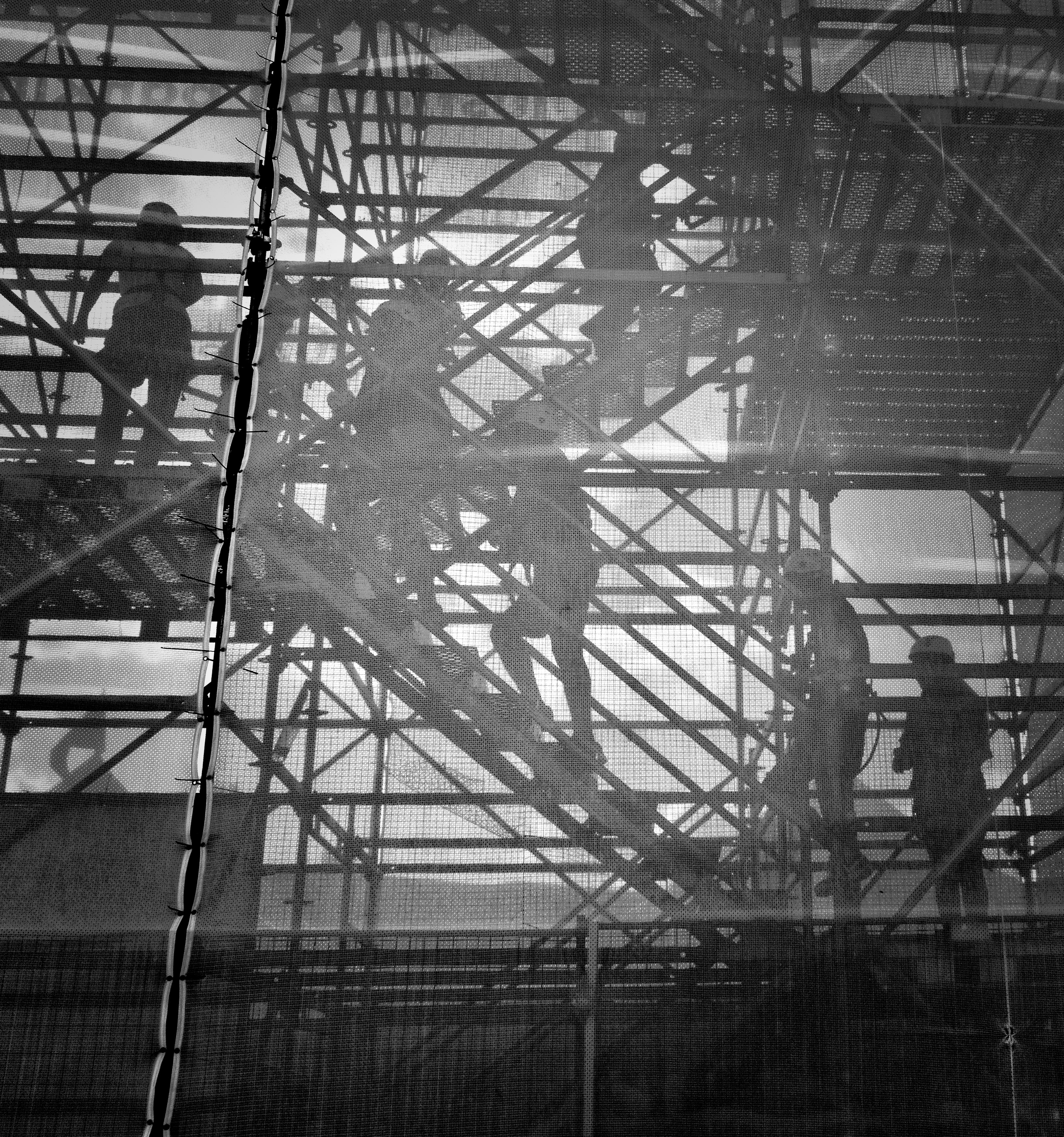 Construction workers walk up scaffolding to their site