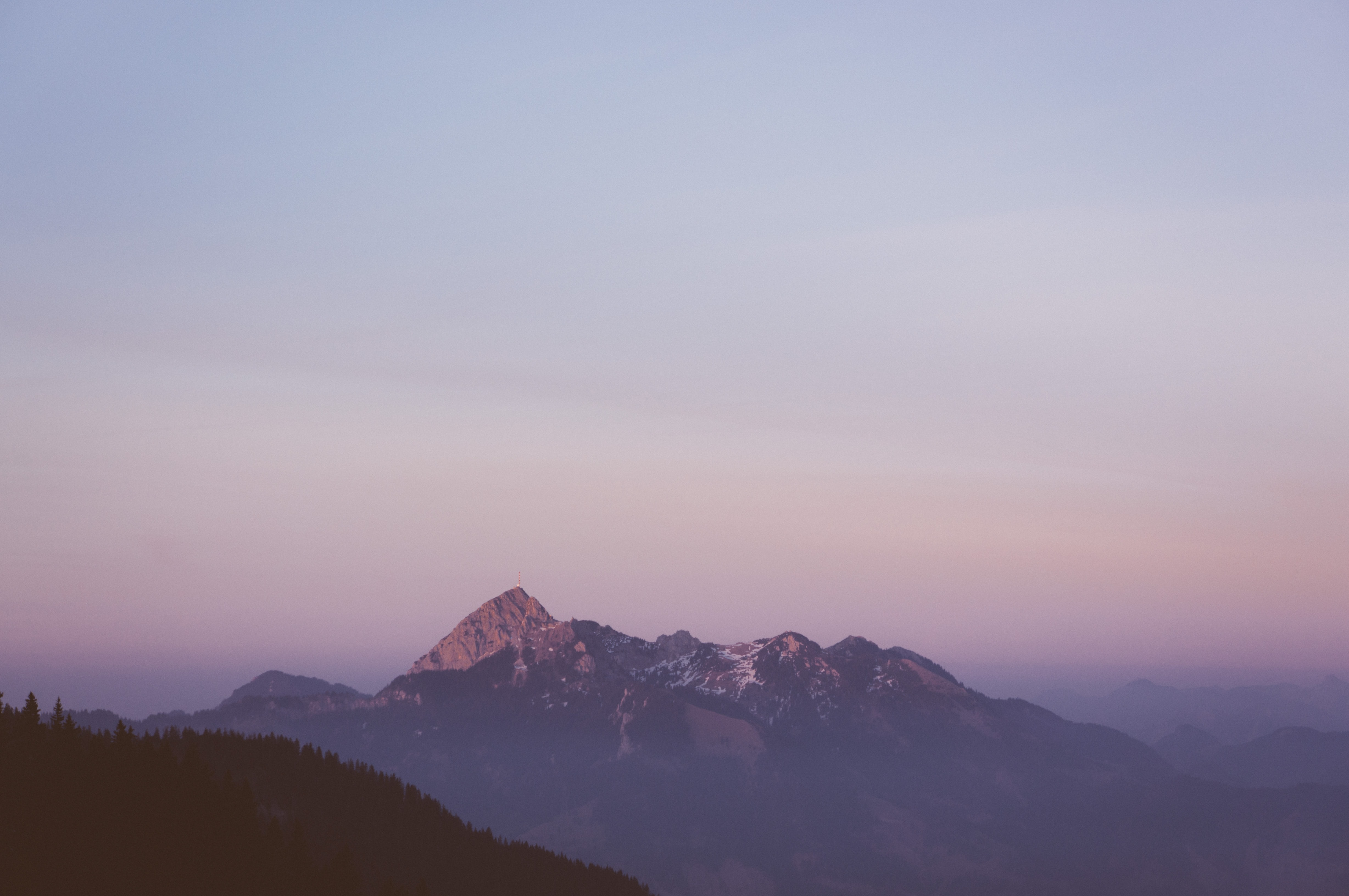 A mountain massif with a radio mast on one of its peaks during sunset