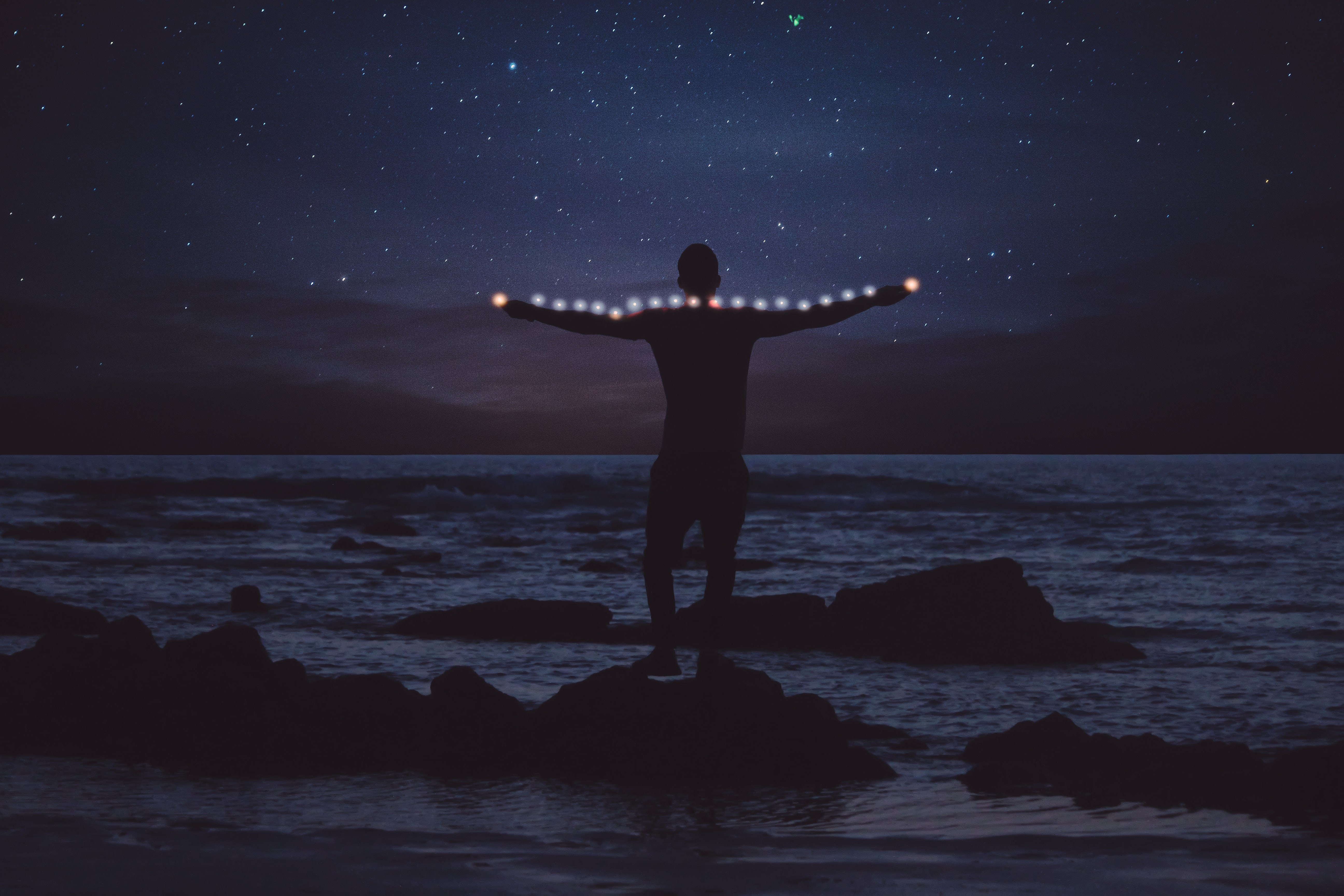 silhouette of person standing on rock on shore stretching string light at night