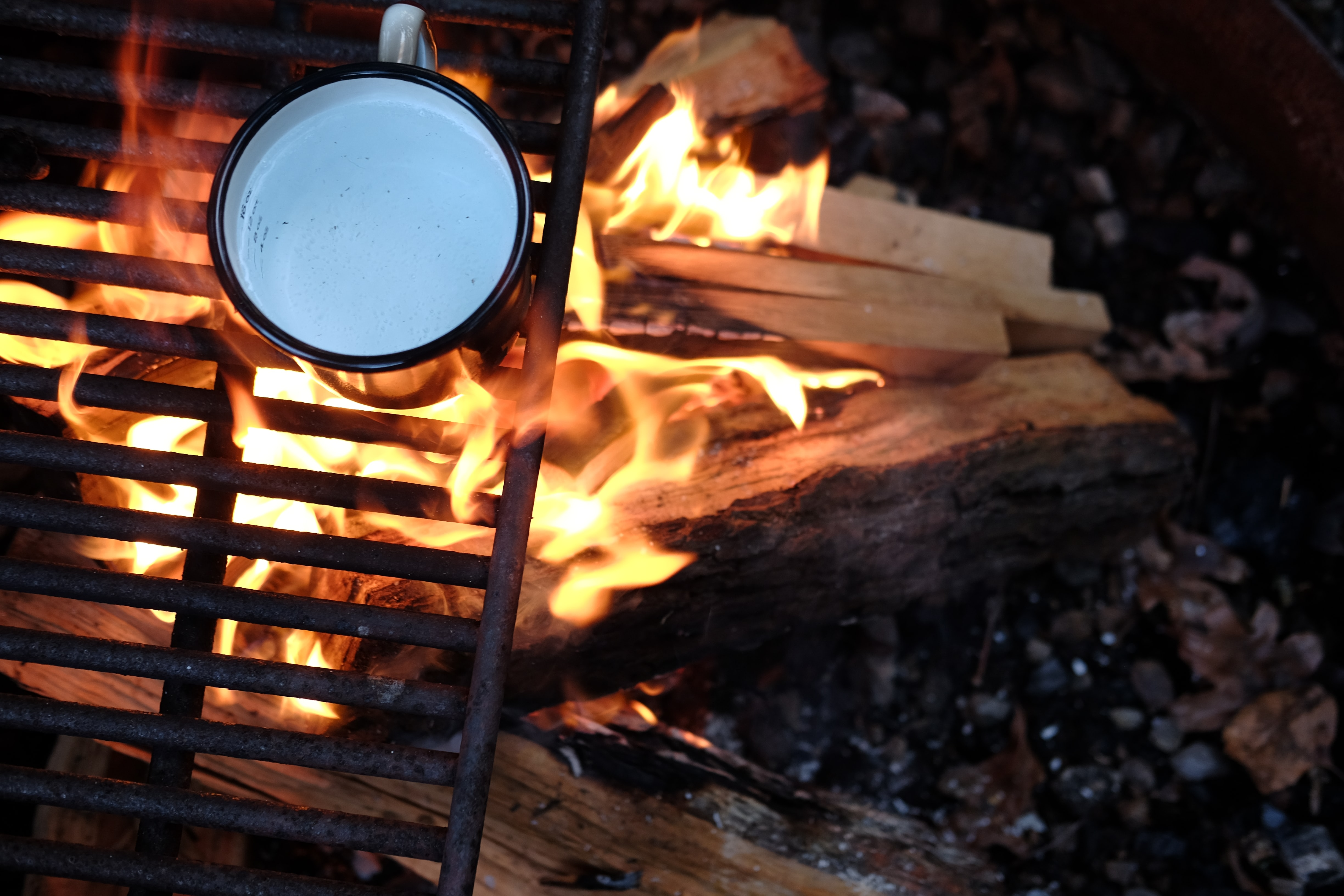 A tin cup of water on a grill above a campfire made of wooden logs in a fire pit