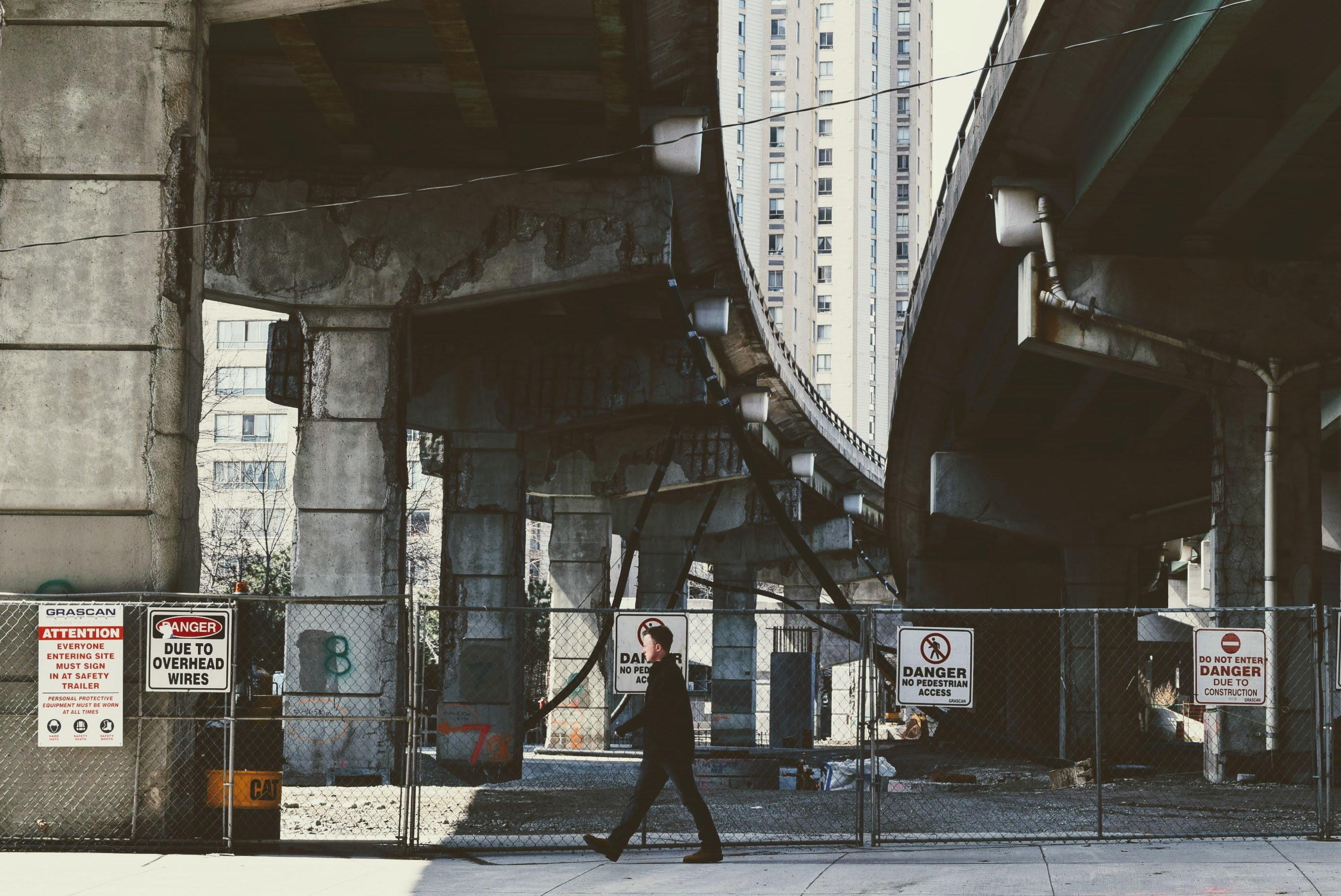 A man walks underneath the overpass along a fenced off area with danger signs.