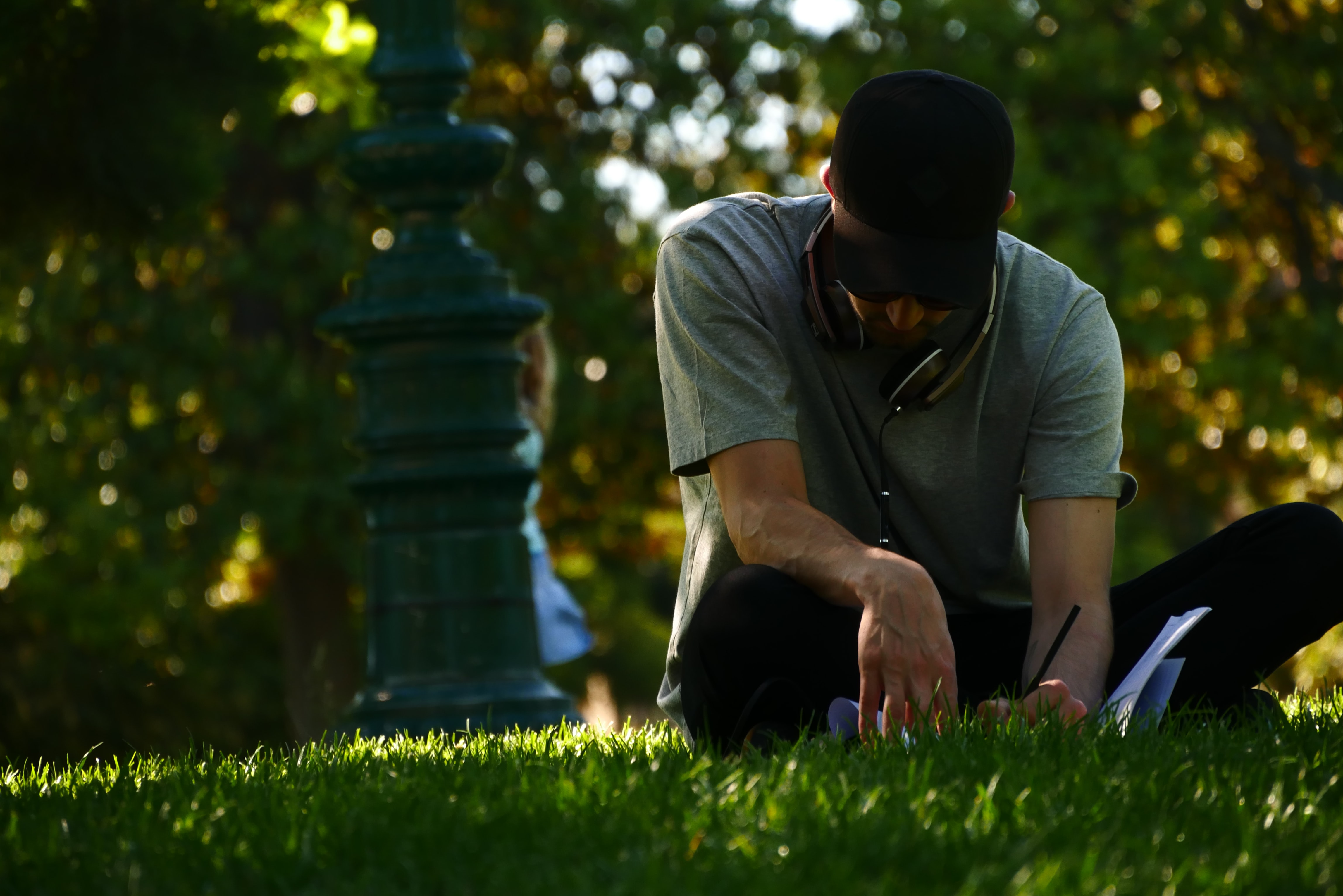 A man wearing headphones and a hat works in the grass