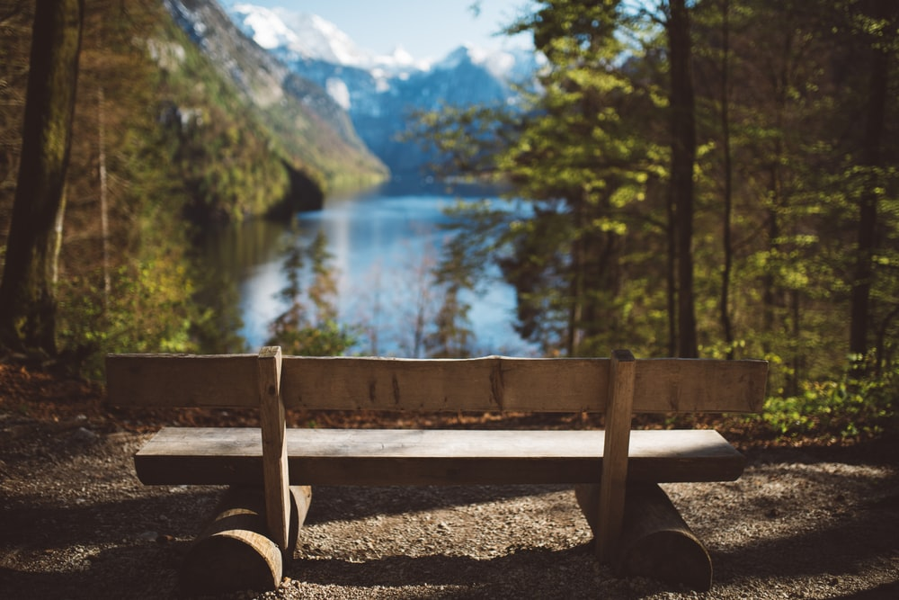 empty brown wooden bench facing body of water and mountain