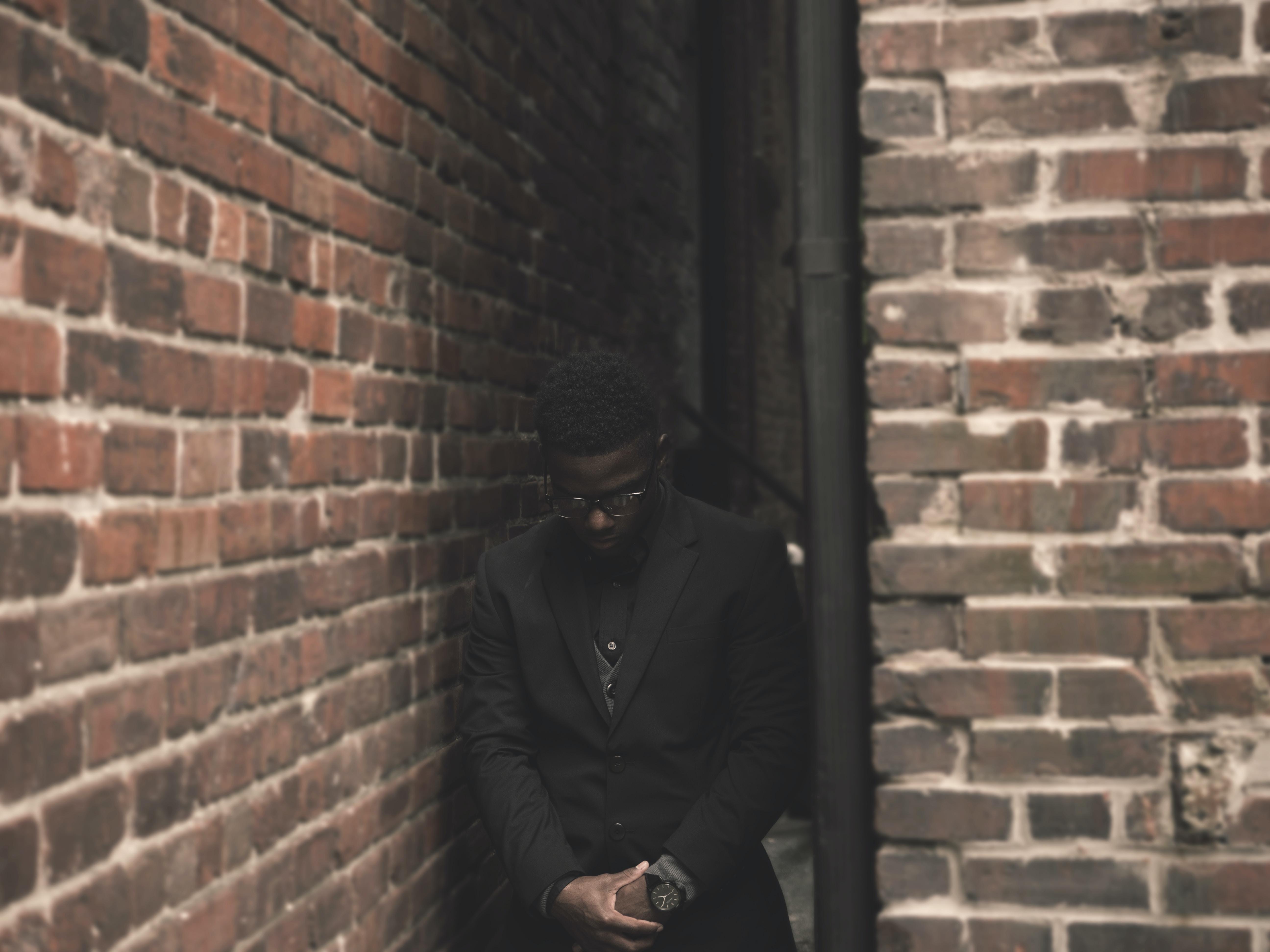 man in black suit standing on corner during daytime