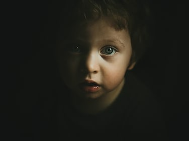 portrait of a young curious child with big eyes standing in the shadows