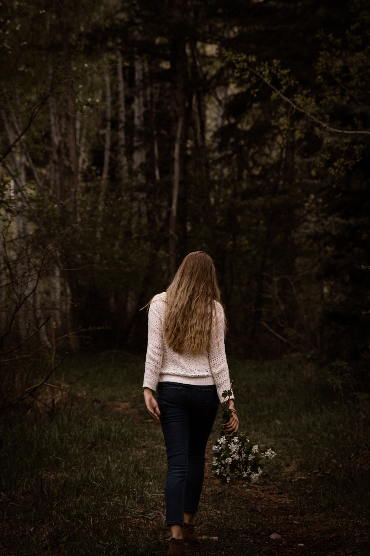 woman wearing white sweater and black pants walking near trees