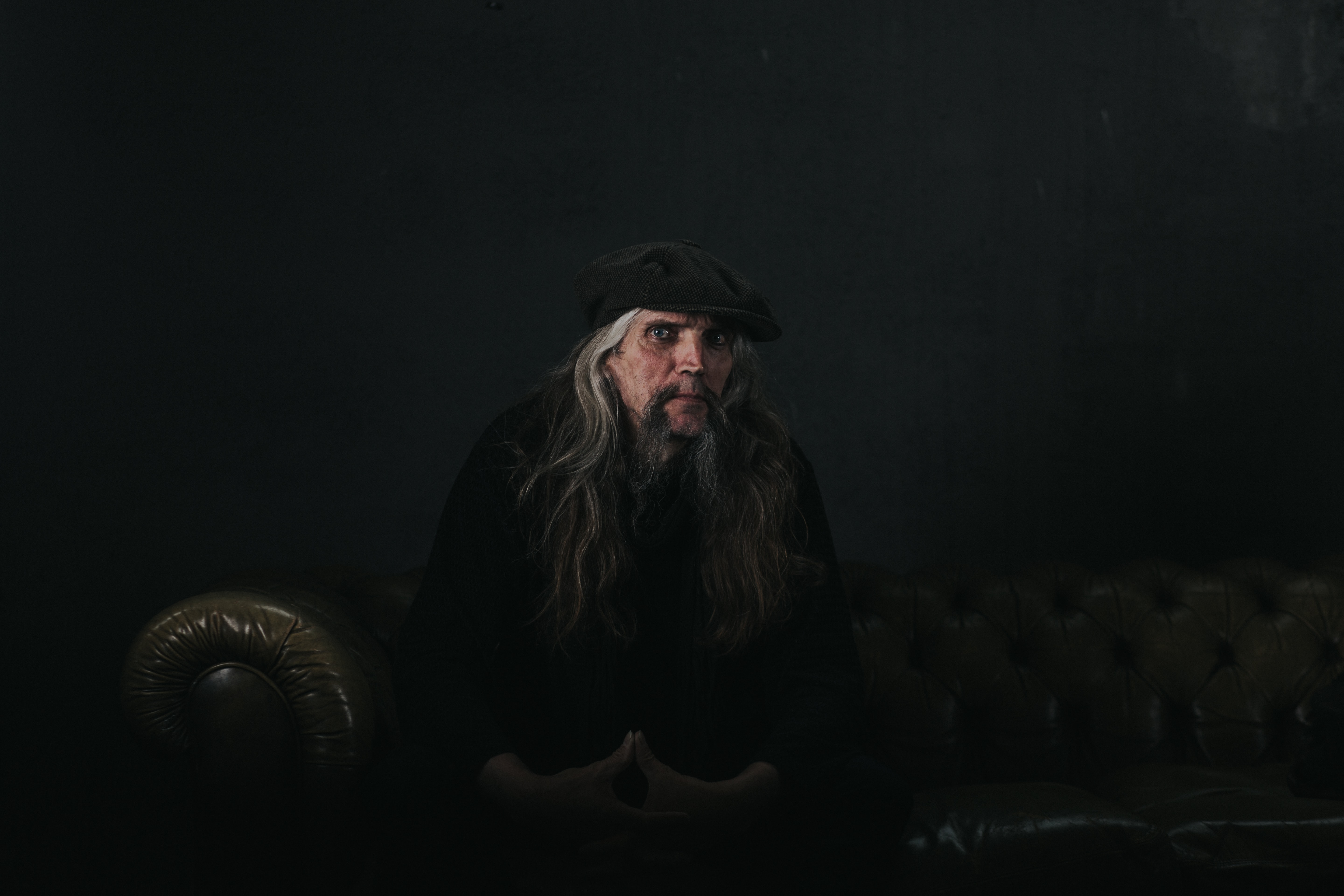 A man with long gray hair sits on a couch against a black background