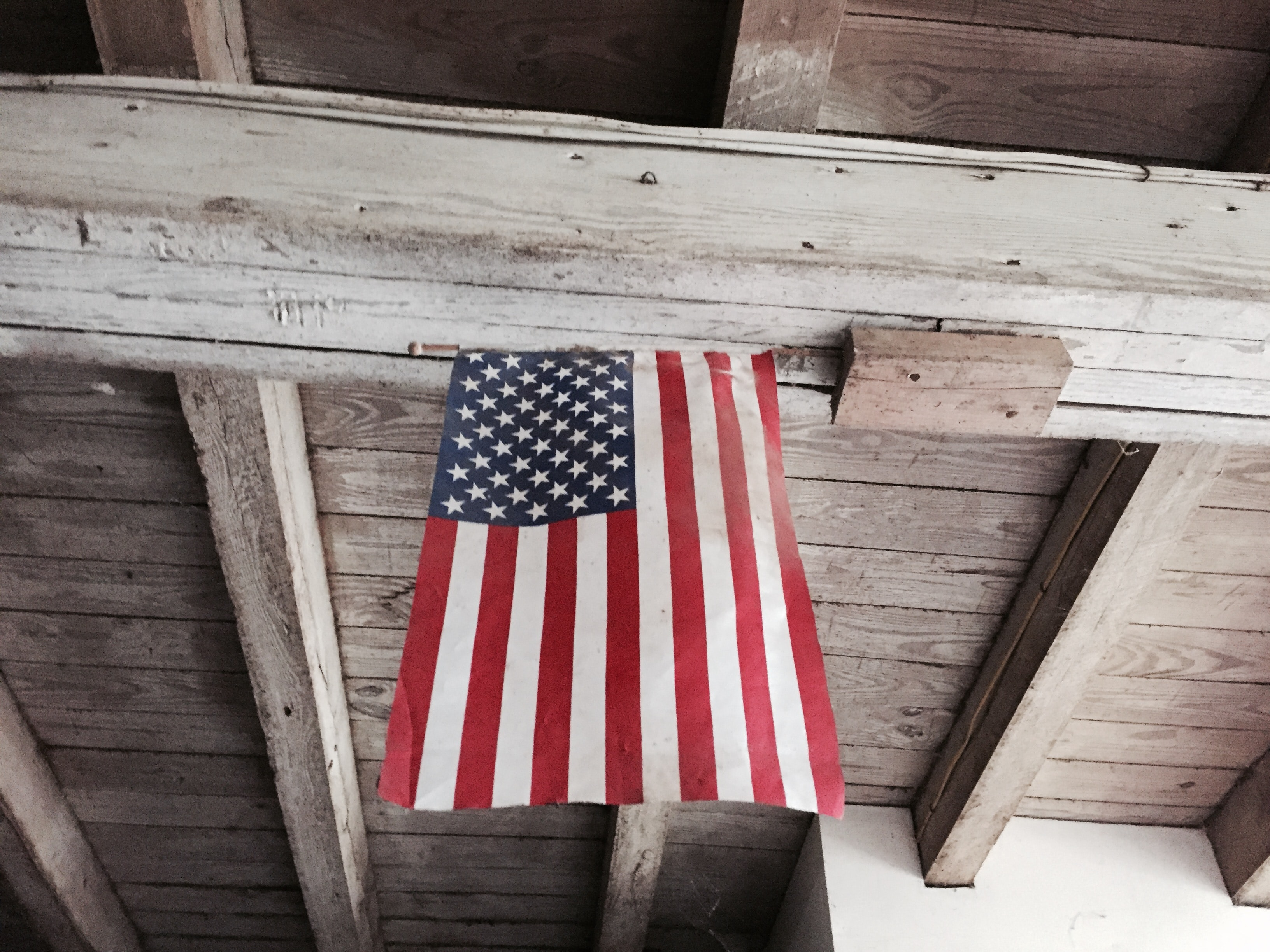 The American flag hanging from a wooden ceiling