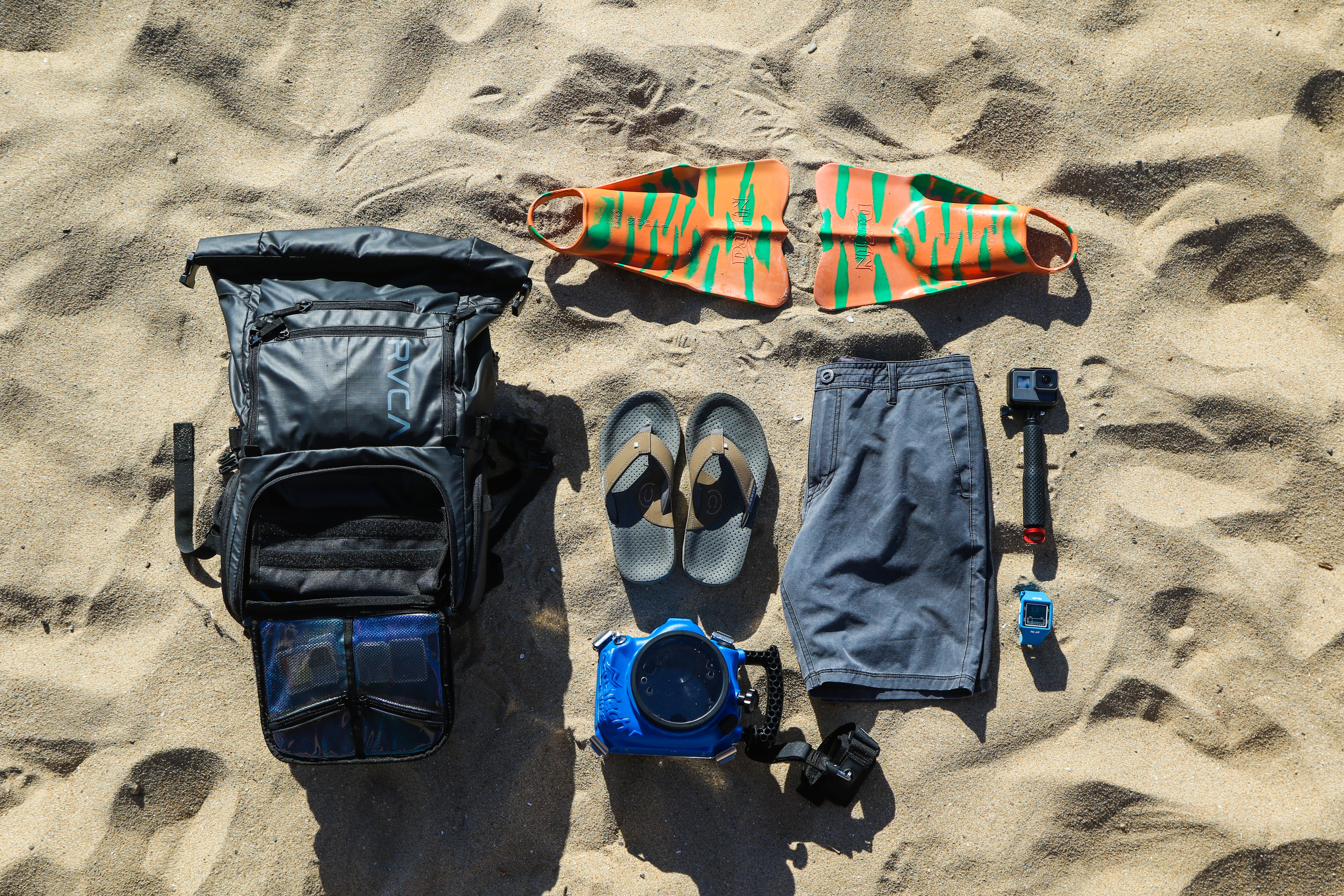 Backpack, shorts, flippers, fins, underwater camera and a GoPro at the sand beach