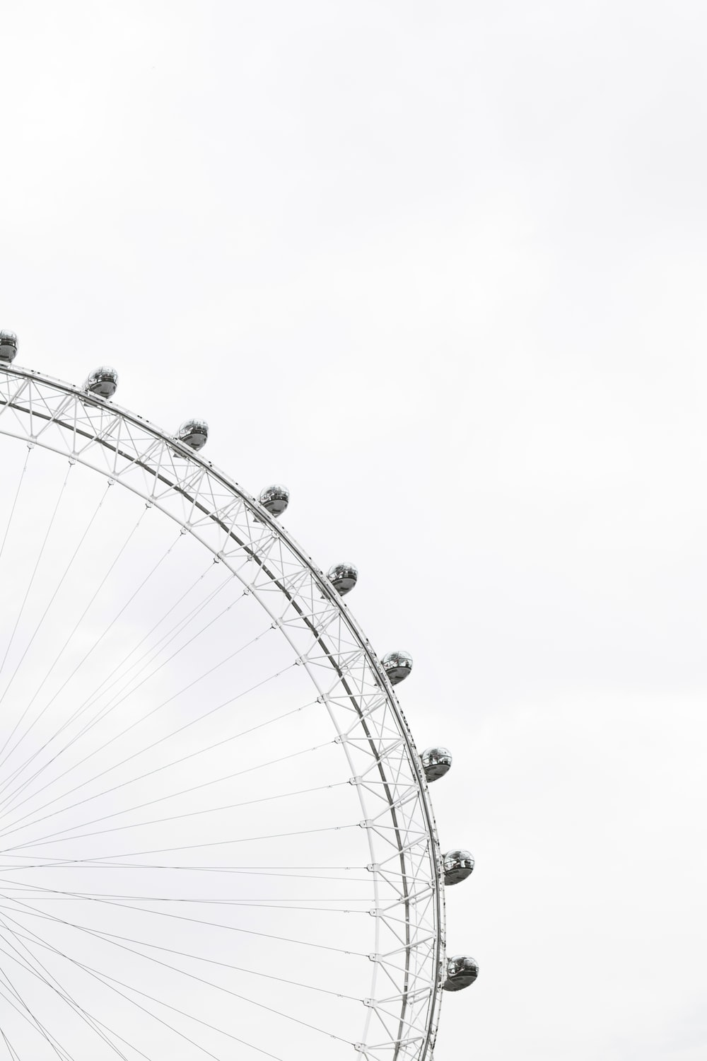 Part of a ferris wheel with enclosed cars for riding in and people in the cars against an overcast sky