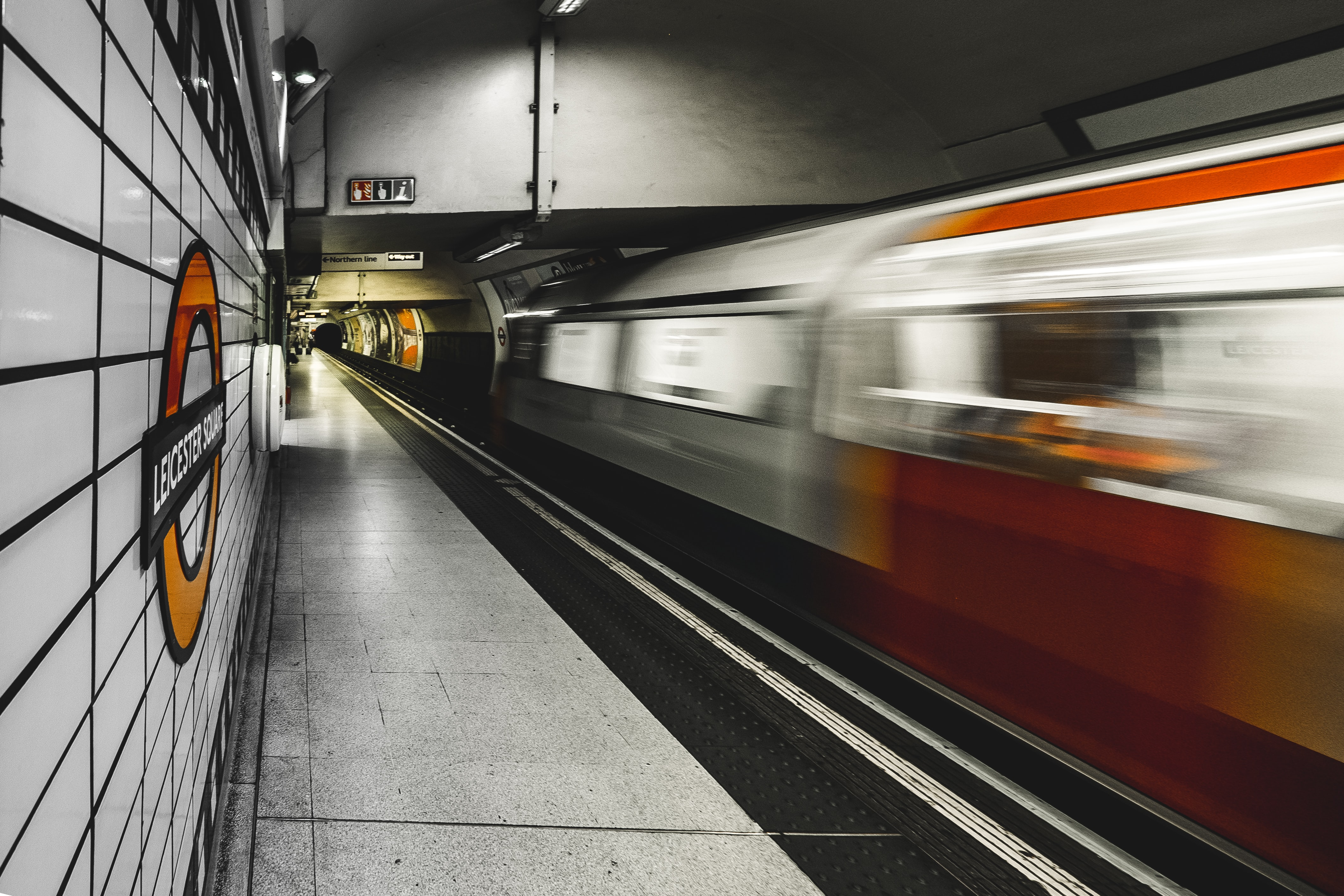 A blurry shot of a moving train from the platform in Leicester Square Station.