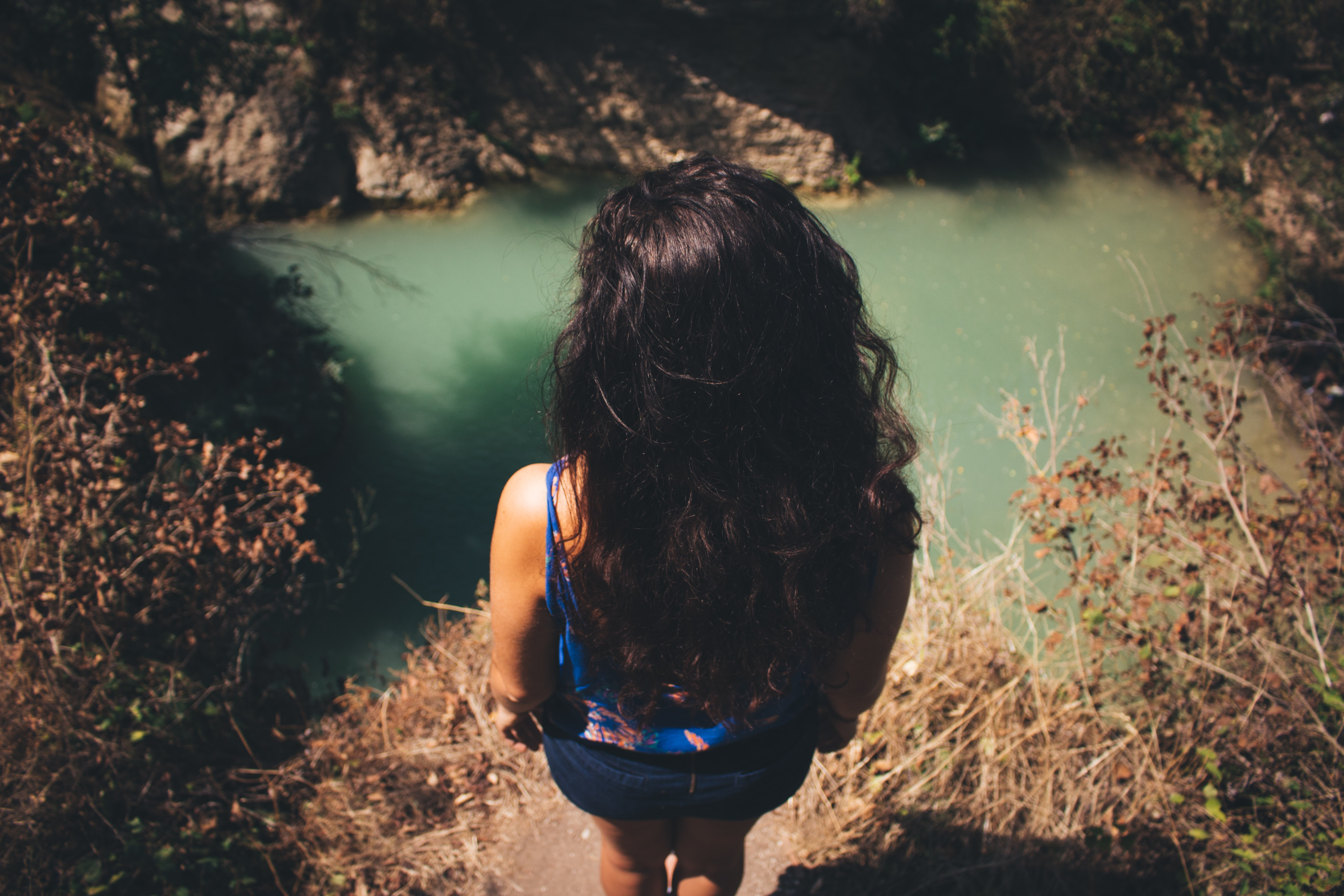 Woman with long hair stairs down at a secluded pond