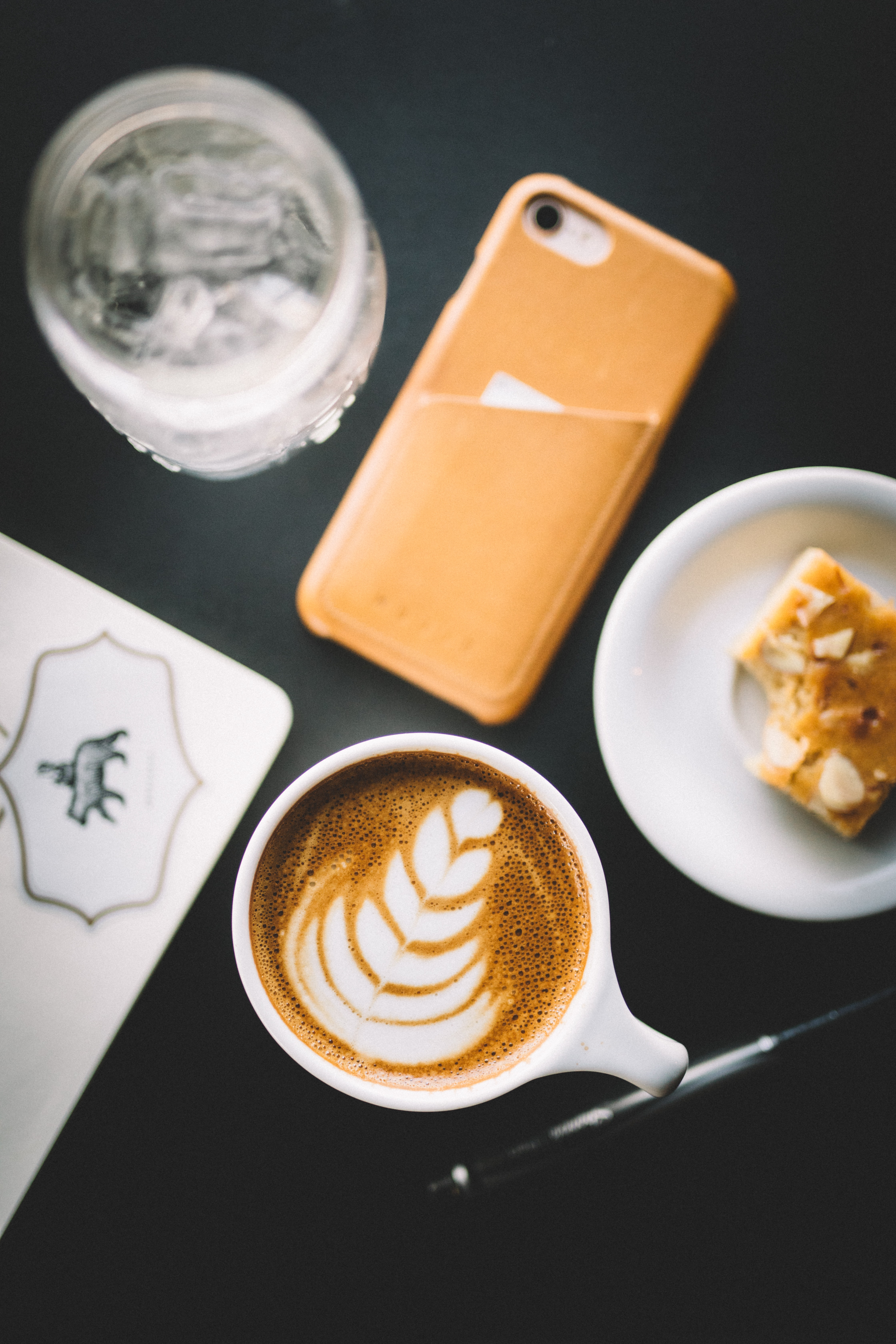 An overhead shot of coffee with latte art on it next to a piece of cake and an iPhone
