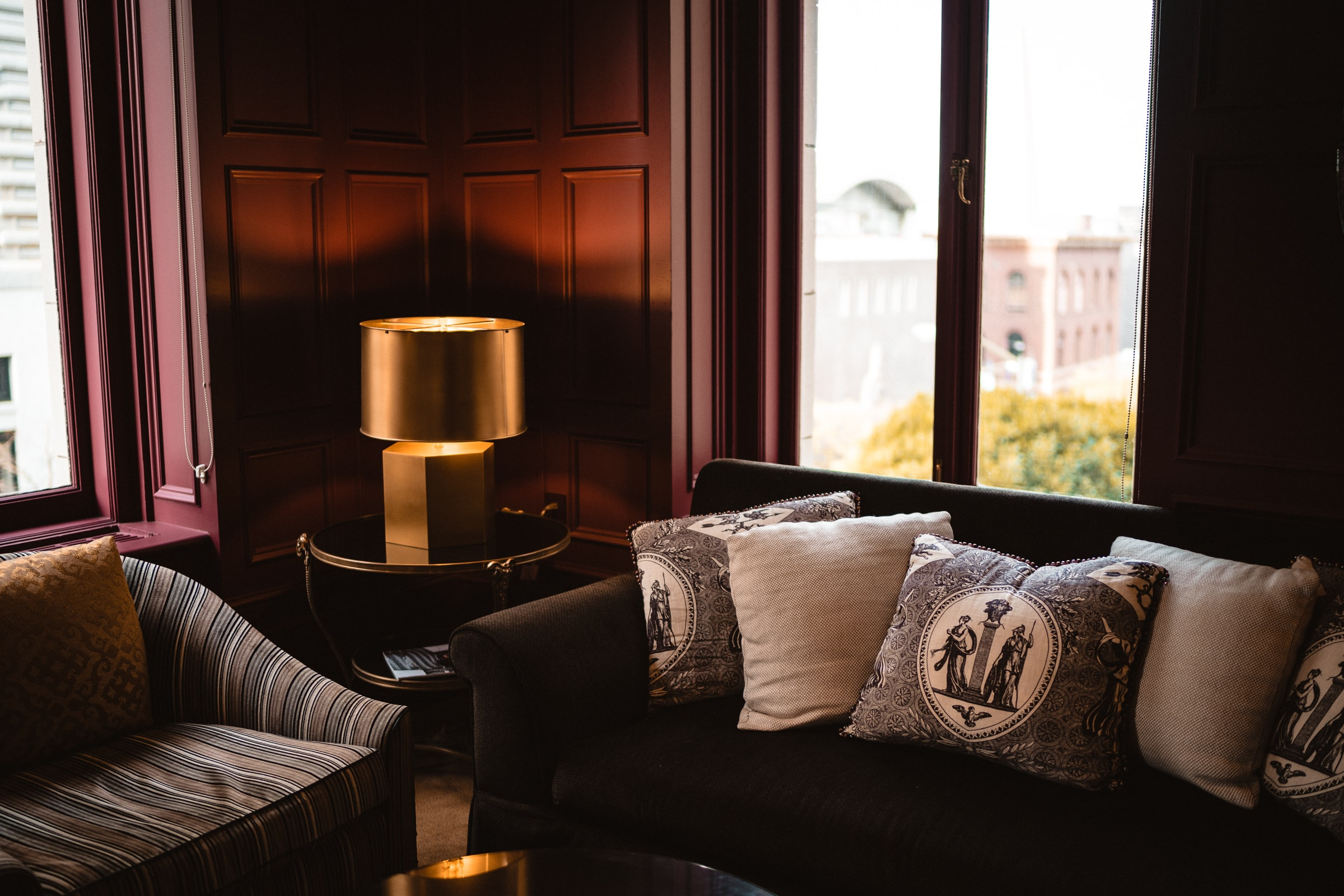 Corner of a room with a gold lamp, two couches, and decorative pillows overlooking brick buildings