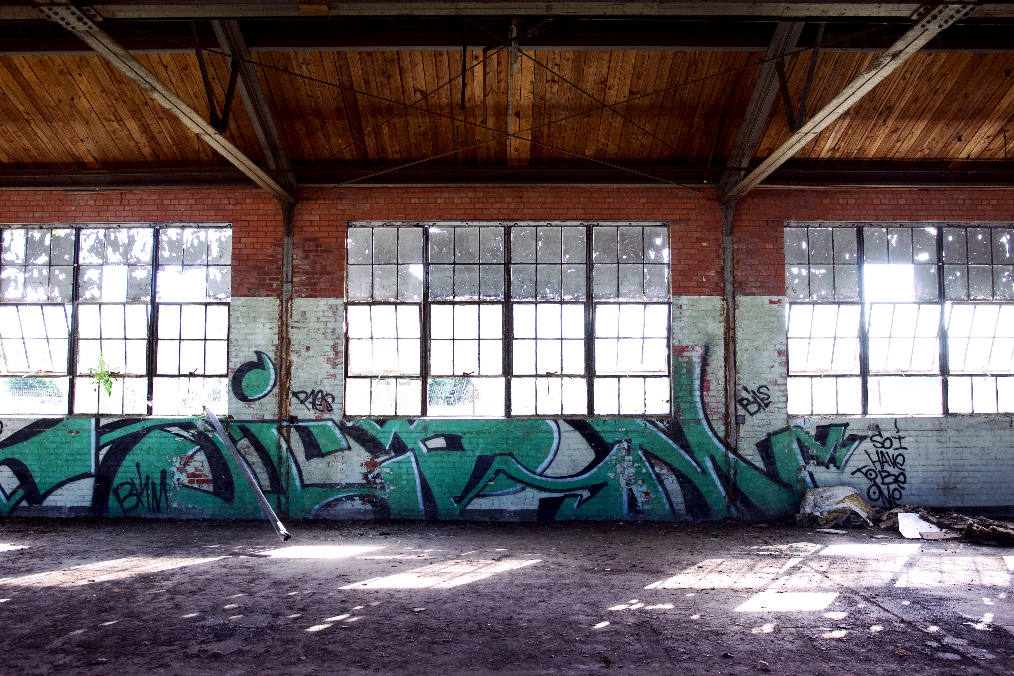 Inside an empty old building with graffiti, large windows, and wooden rafters.
