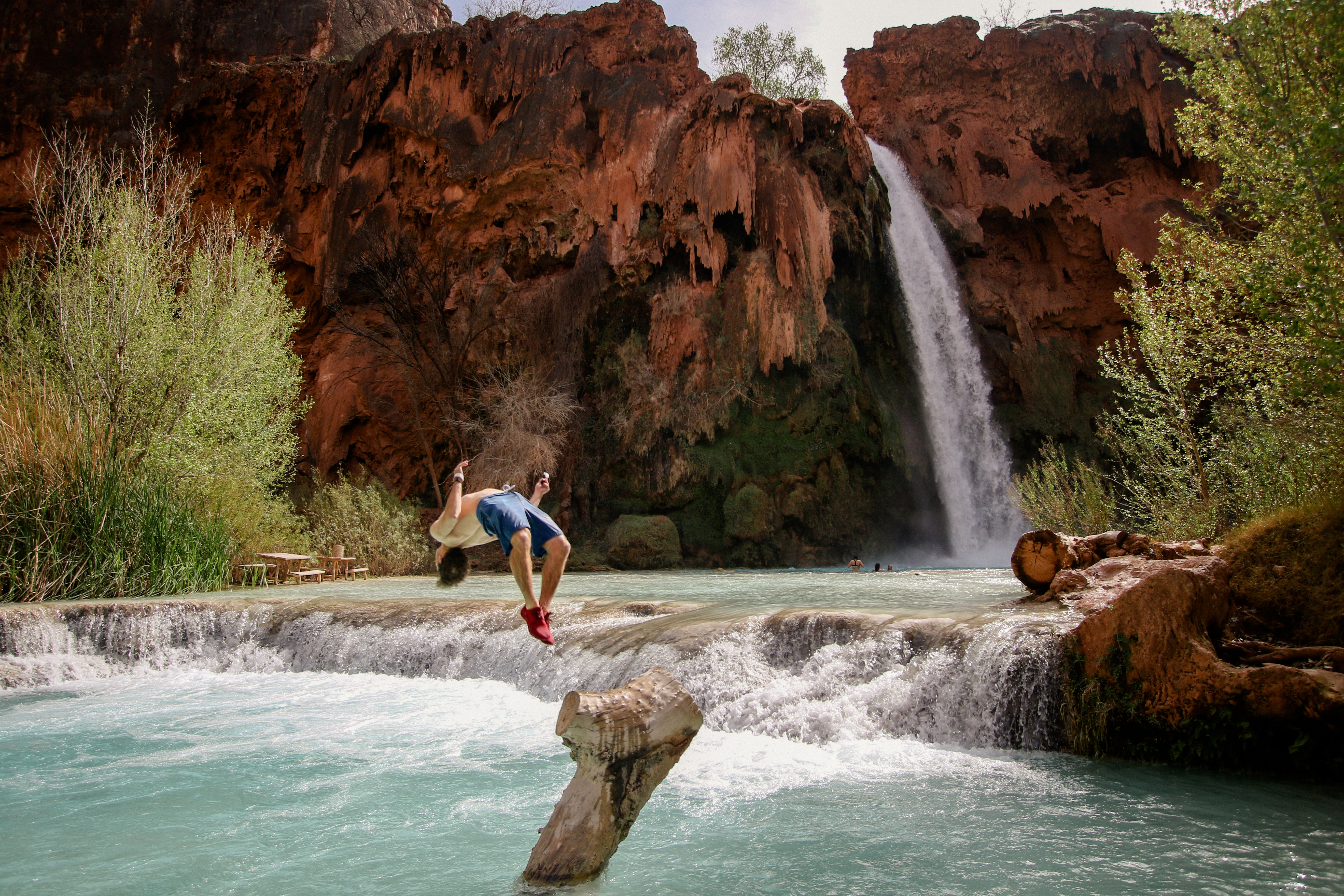 A person does a backflip into the water at a mountain pond at the bottom of a tall waterfall