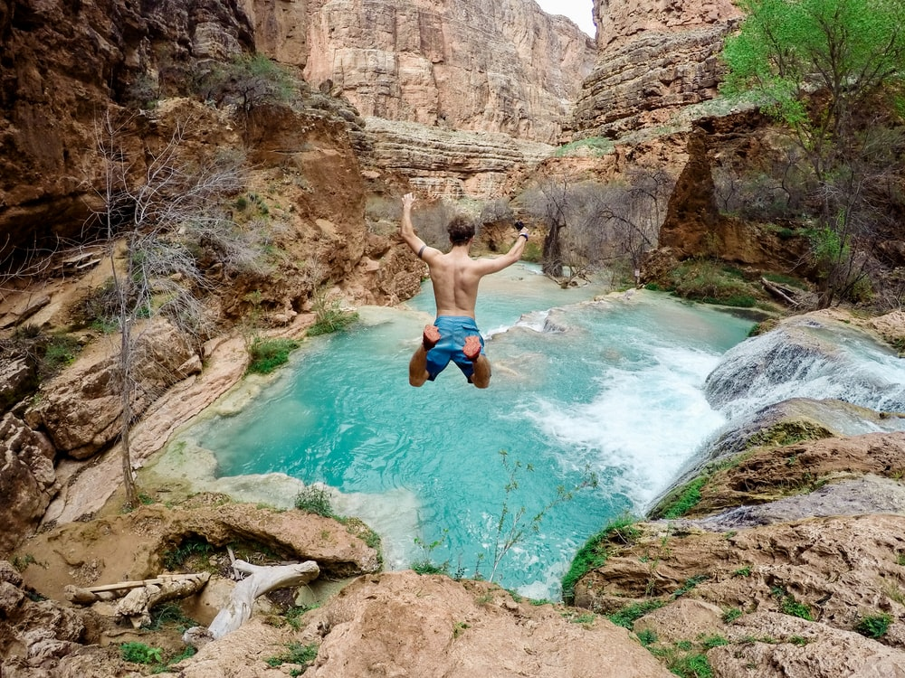 time lapse photography of man jumping on waterfalls