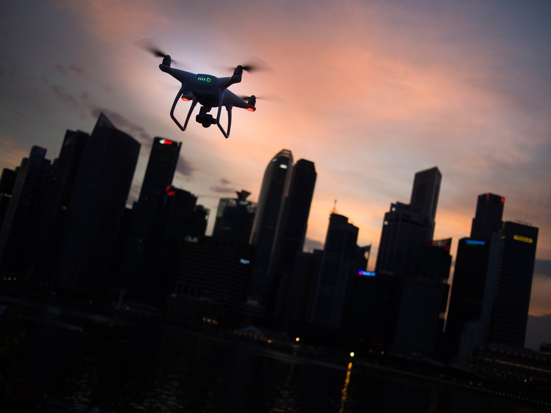 A drone flying in the sunset sky with a city skyscape in the distance
