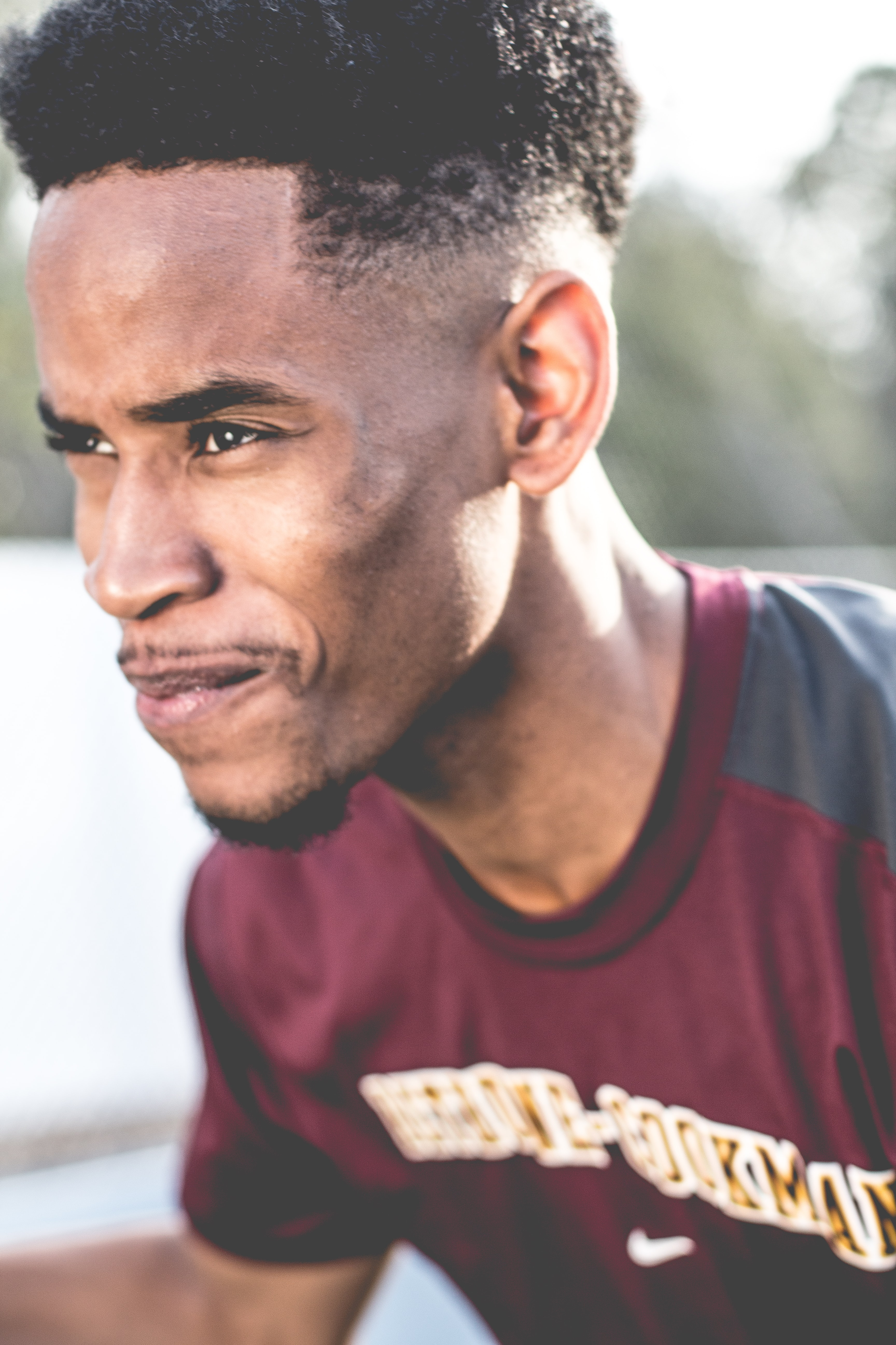 A close-up view of a man in a maroon sportswear.