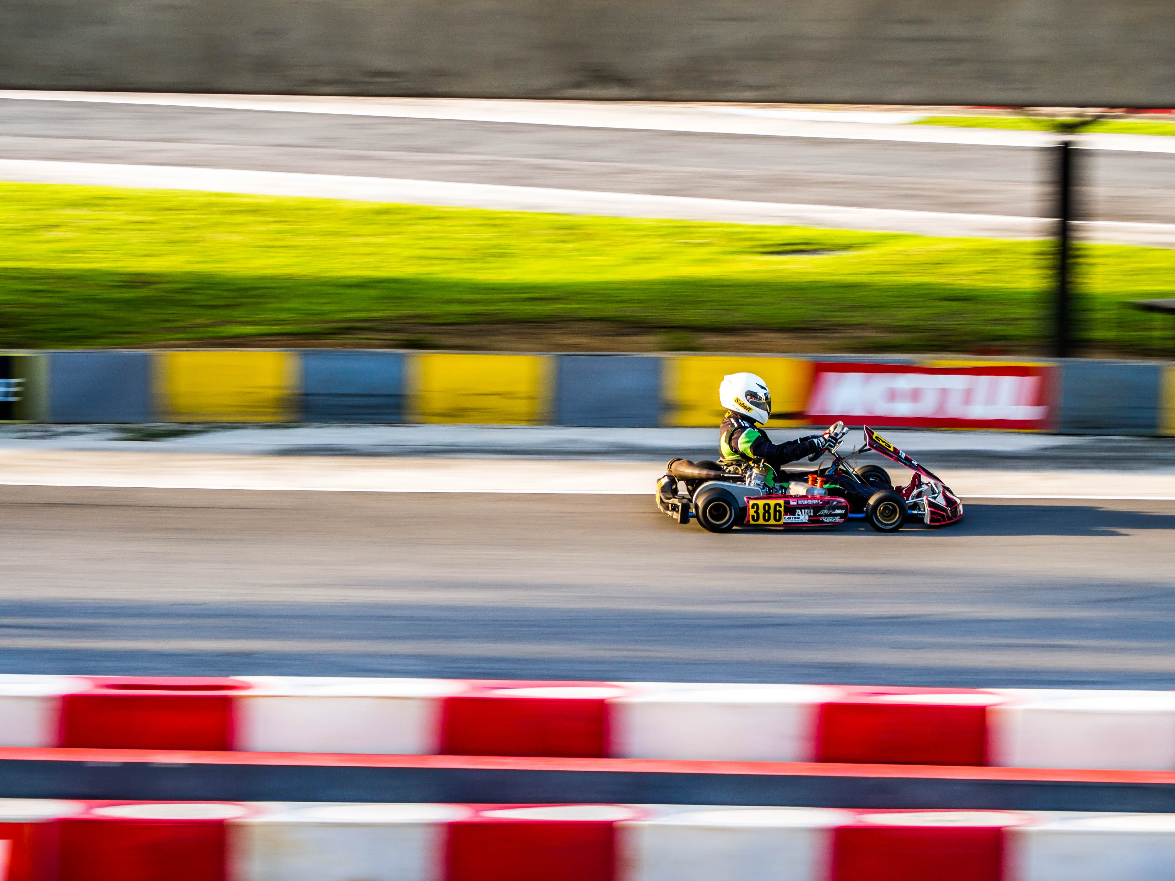 A blurry shot of a person driving a go-kart on race track