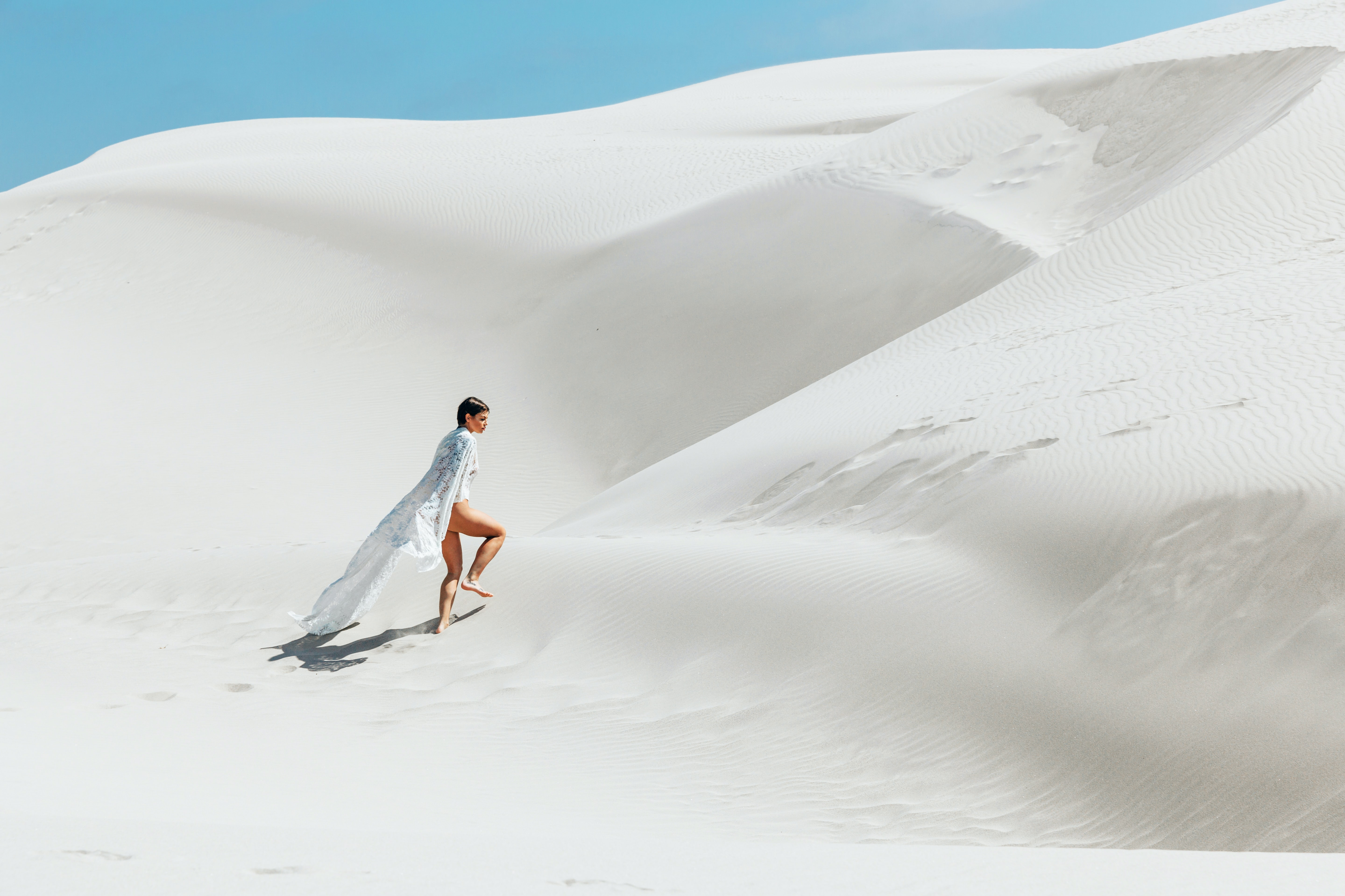 woman walking on white sand dunes