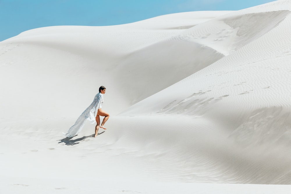 woman walking on white sand dunes