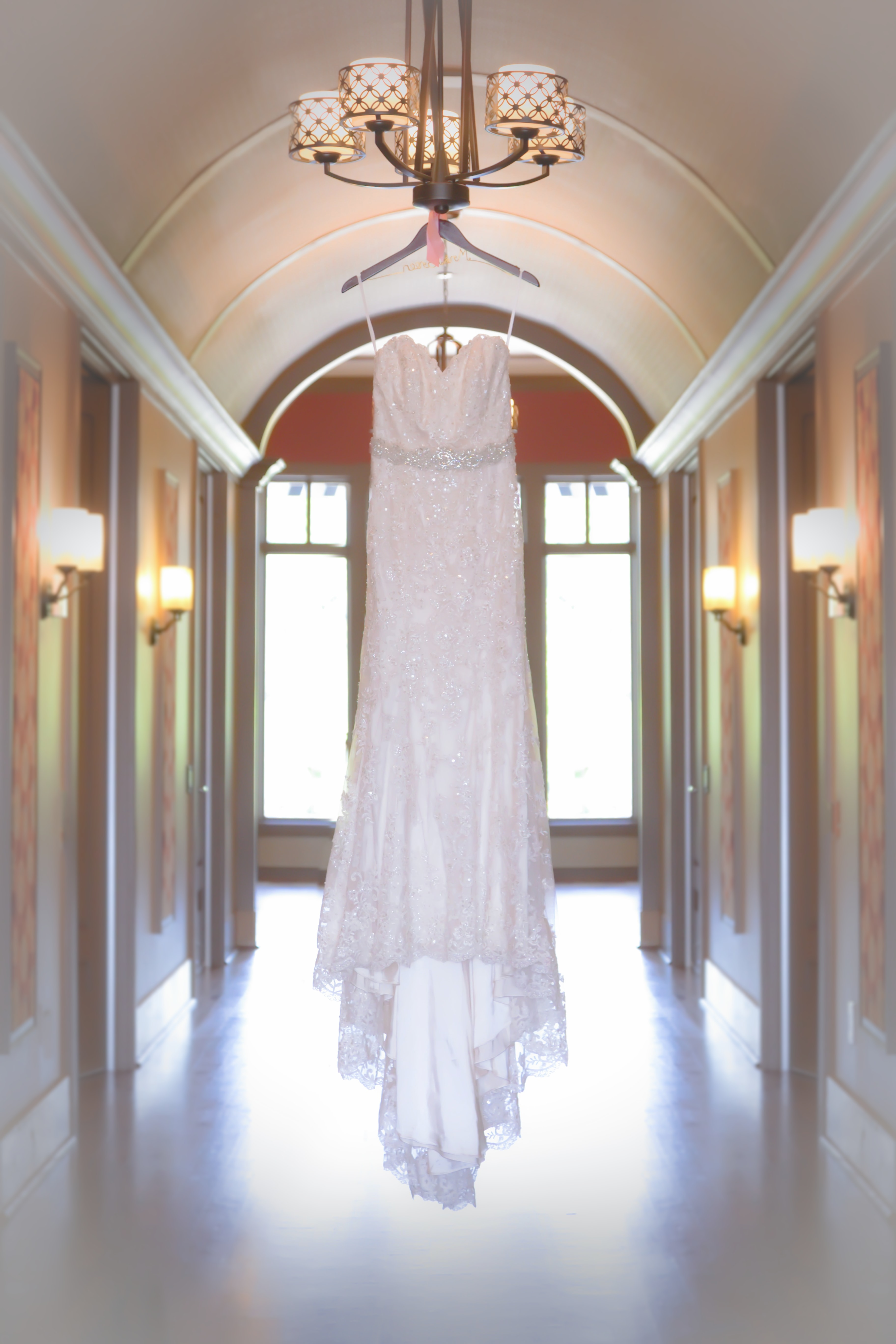 Thin wedding dress hangs from Chandelier in arched hall