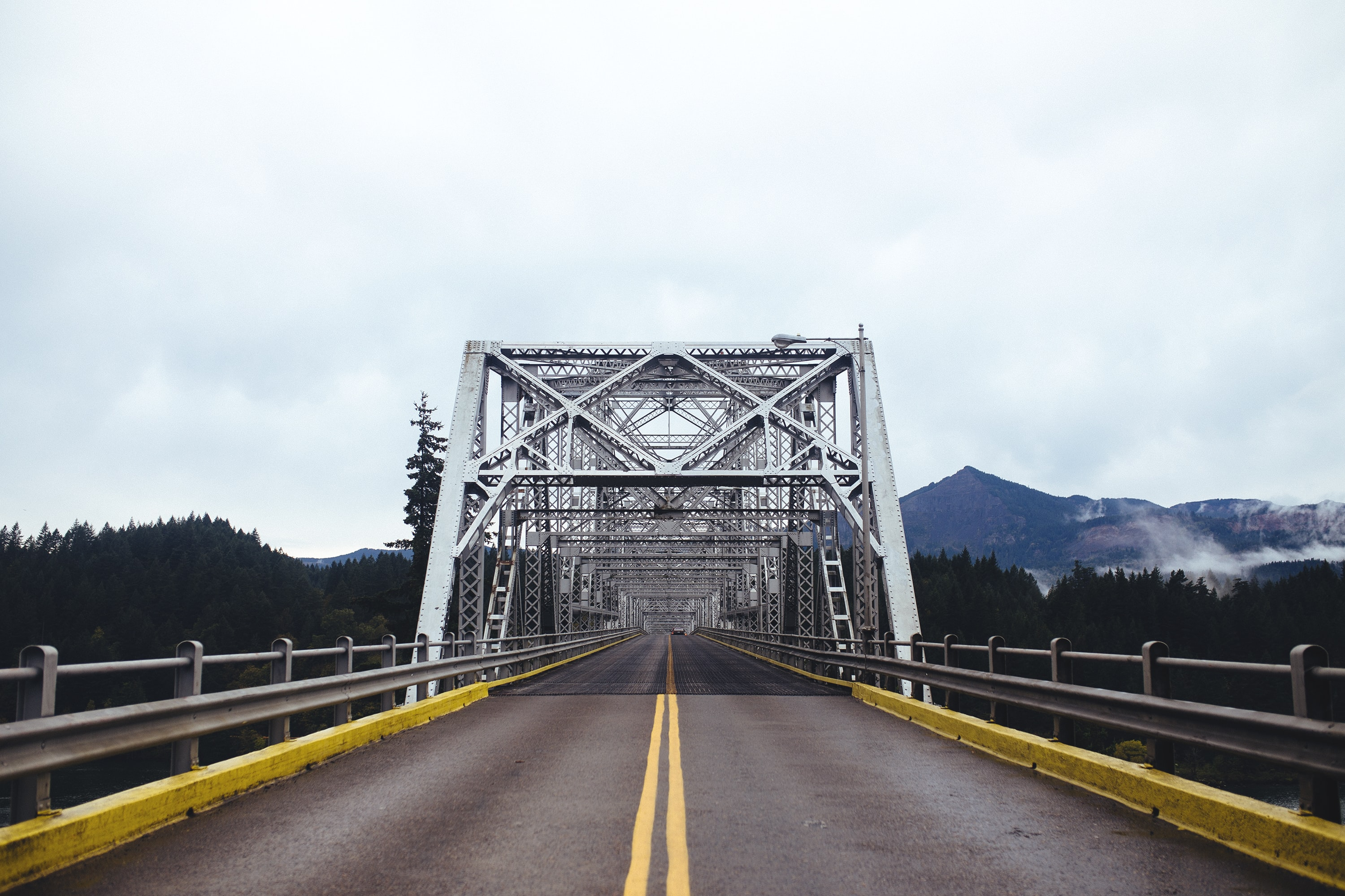 white and gray steel bridge with two yellow lanes