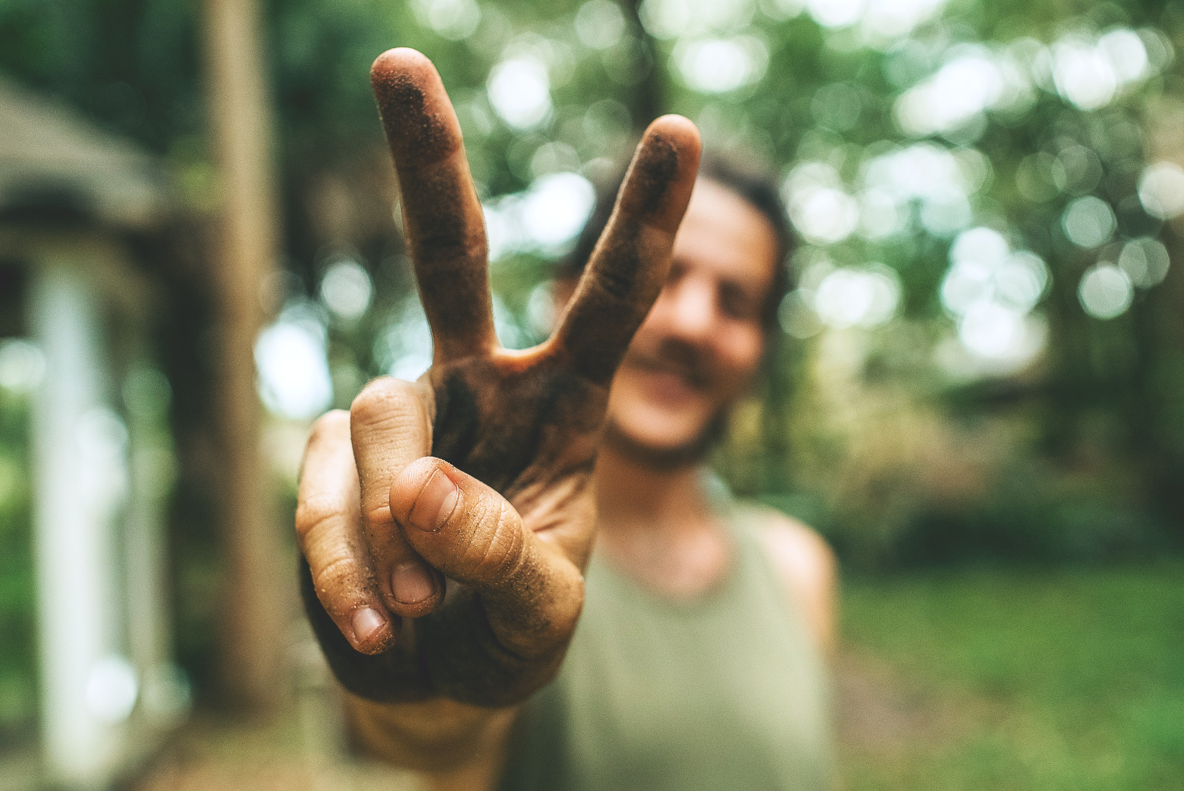 Man extends a peace sign with dirty hands in the wood