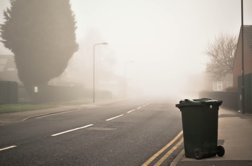 black trash can with wheel near gray asphalt road during daytime