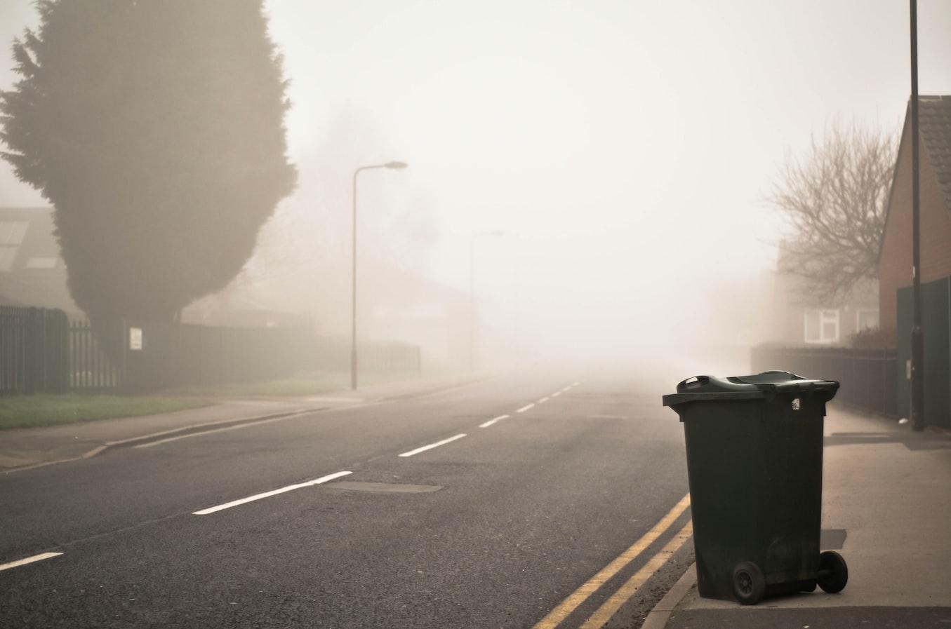 Mülltonne steht an der Seite einer Straße im Morgengrauen