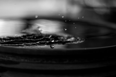 grayscale photography of water spalsh drop teams background