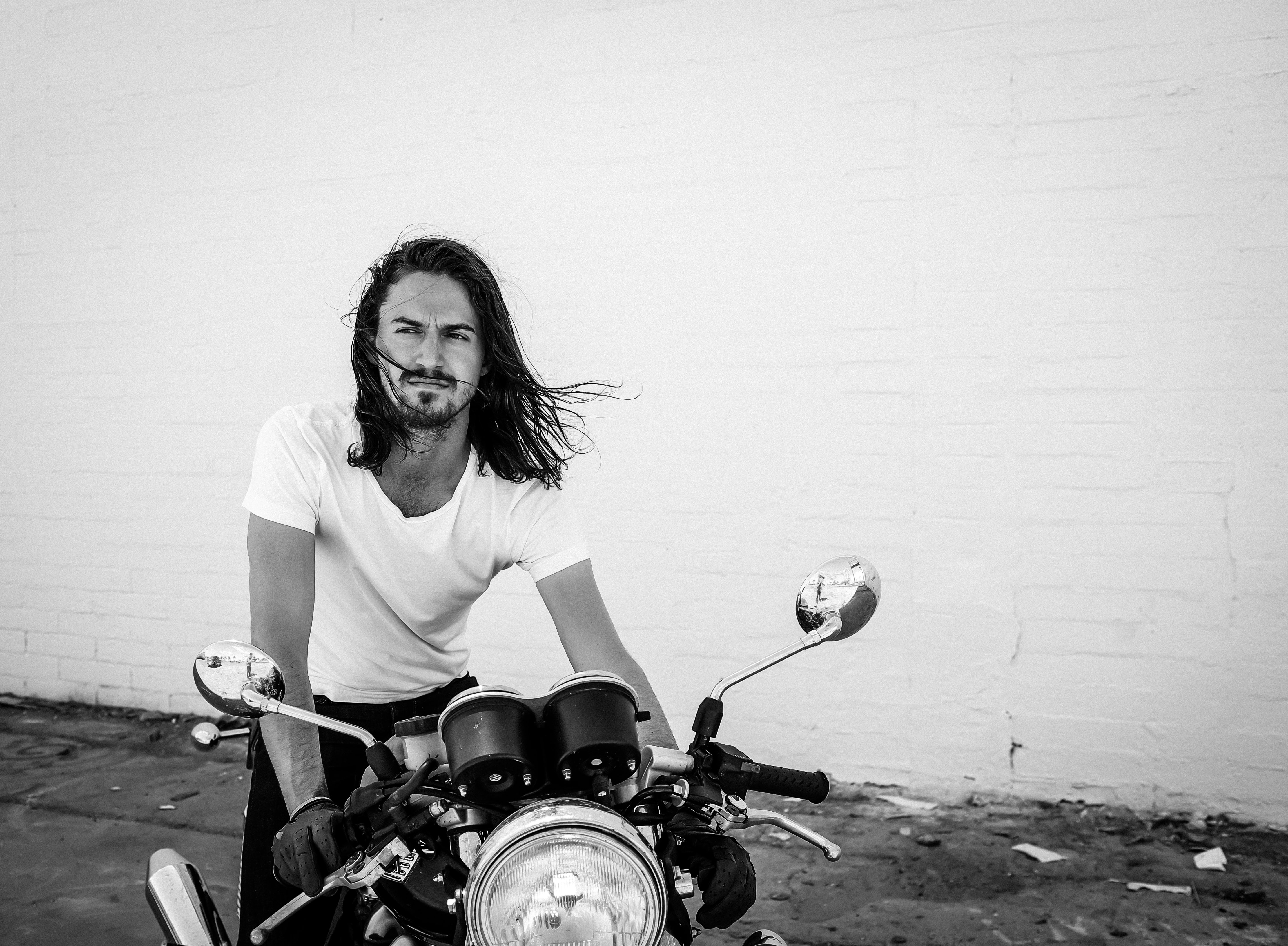 Black and white shot of attractive long haired man in white t shirt with motorbike